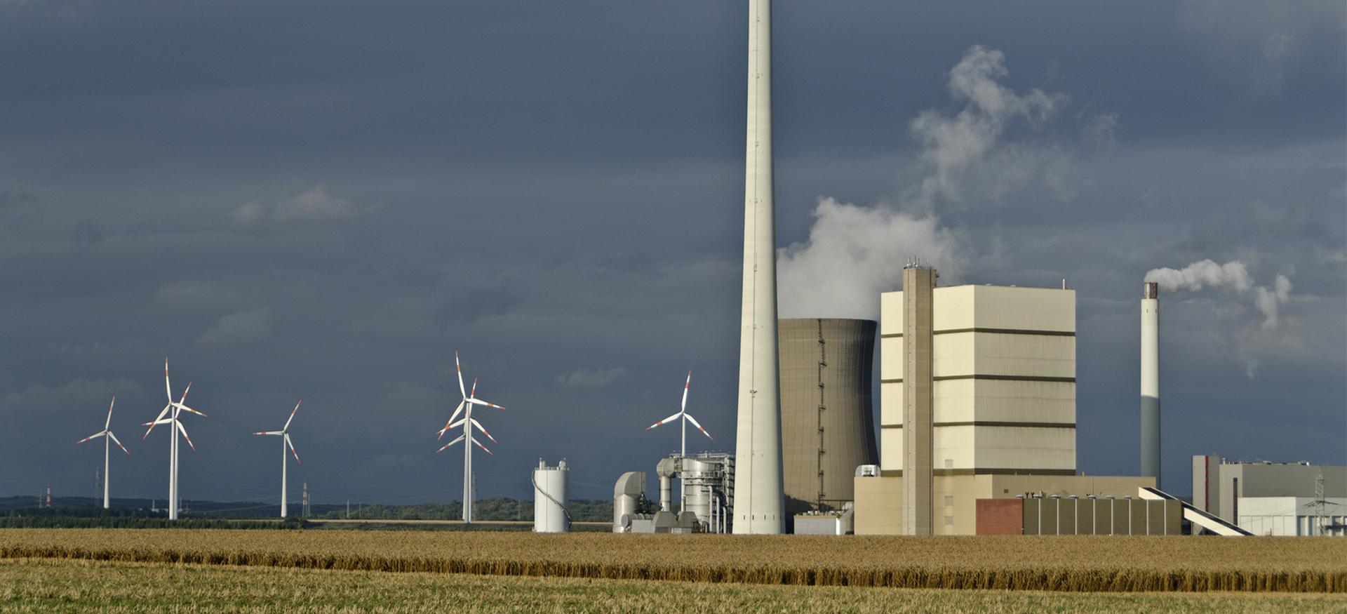 Kraftwerk mit rauchenden Schornsteinen und Windkraftanlagen vor dunkelgrauem Himmel auf einem Feld