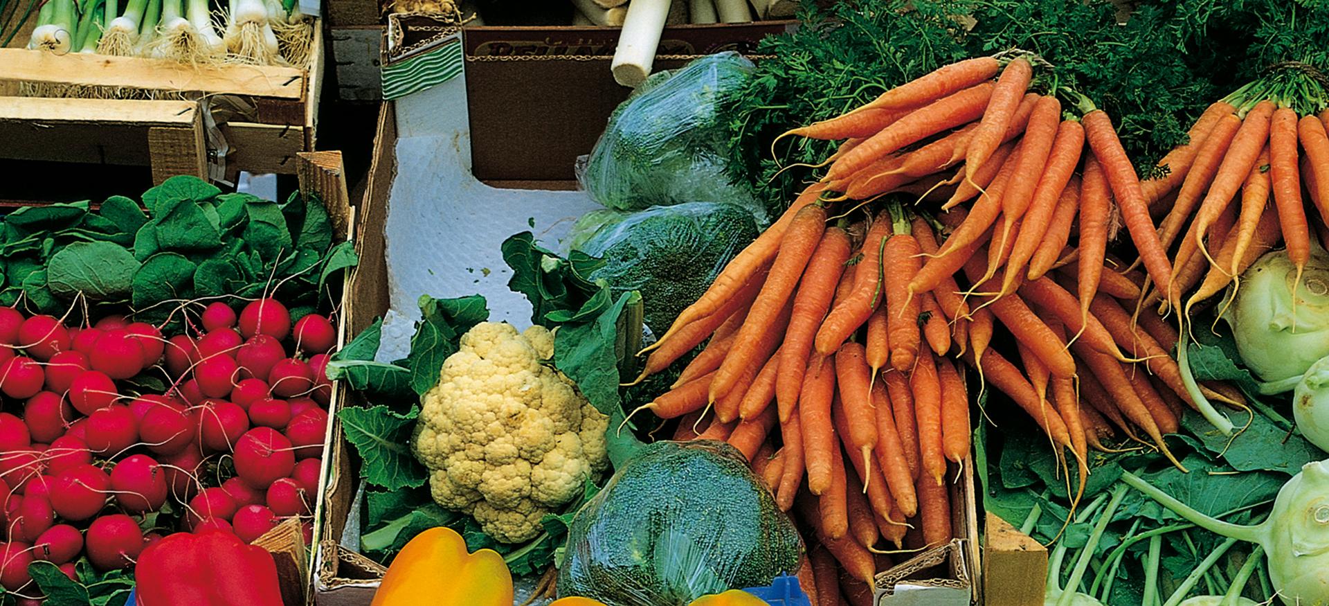verschiedenes Gemüse (Moehren, Radieschen, Paprika, Zwiebeln, Lauch) werden in Holzkästen auf dem Markt angeboten
