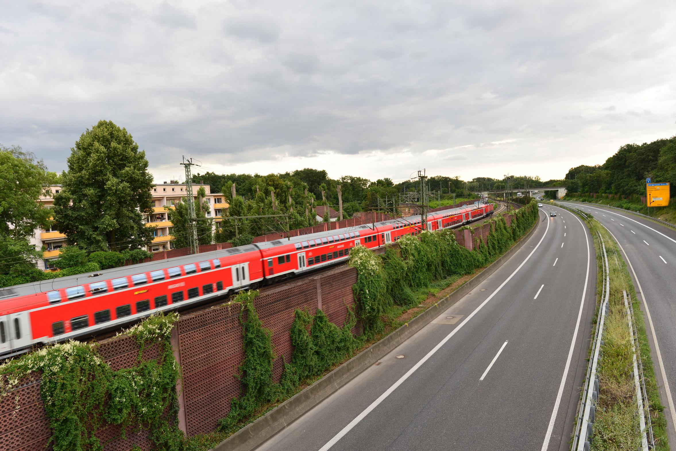 Fahrender Zug neben Bundesstraße nahe einem Wohngebiet