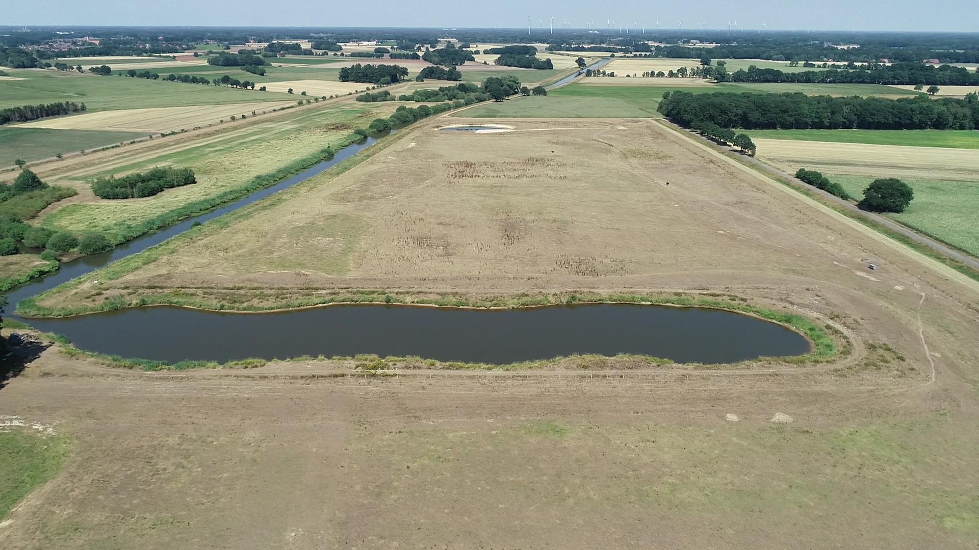Luftbild der Hase und umgebenden Überflutungsräumen. Ein Stillgewässer reicht weit in eine Grünlandfläche hinein.