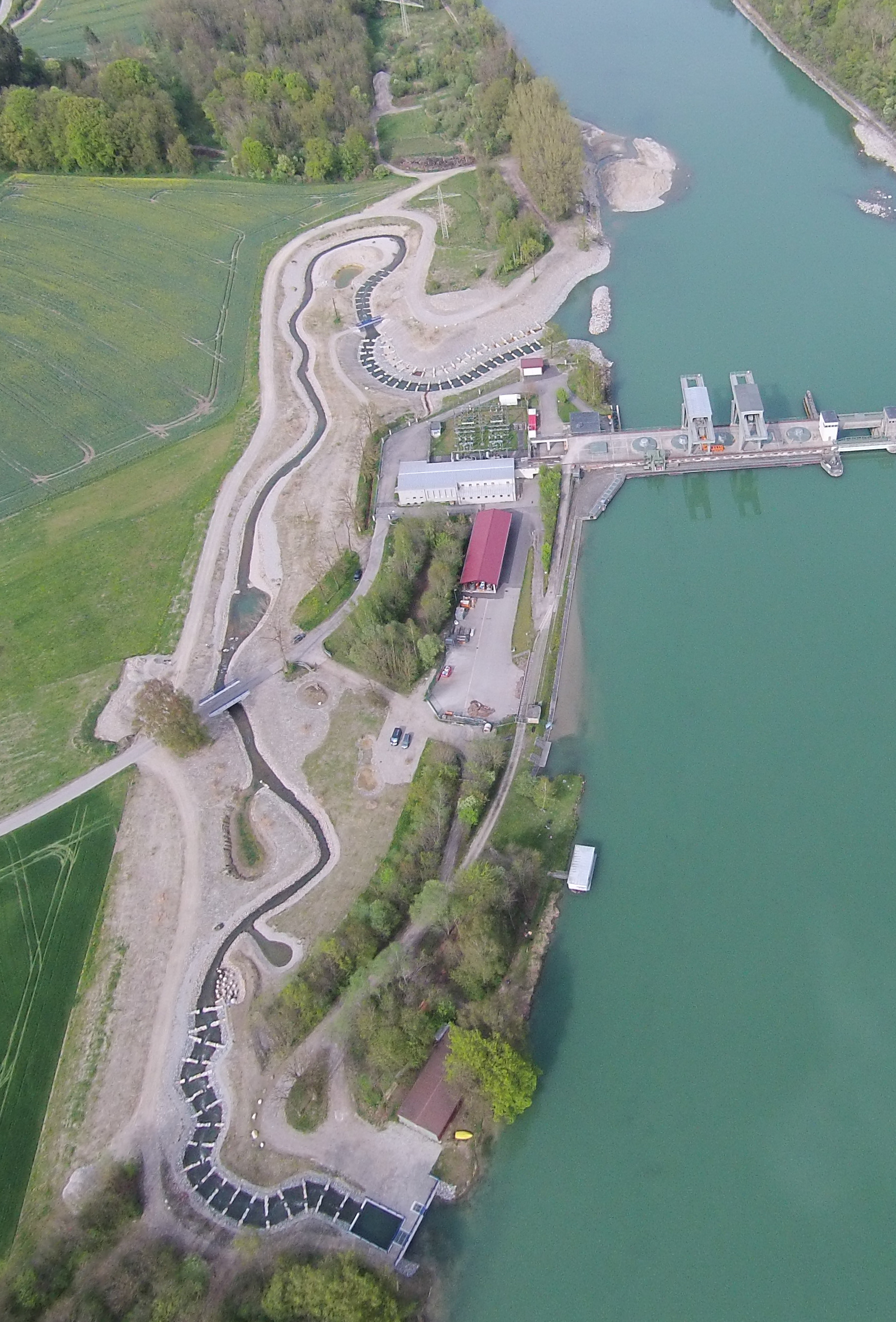 Luftbild des Kraftwerks Gars am Inn, um das ein künstlich angelegtes Umgehungsgewässer für Fische herumführt.