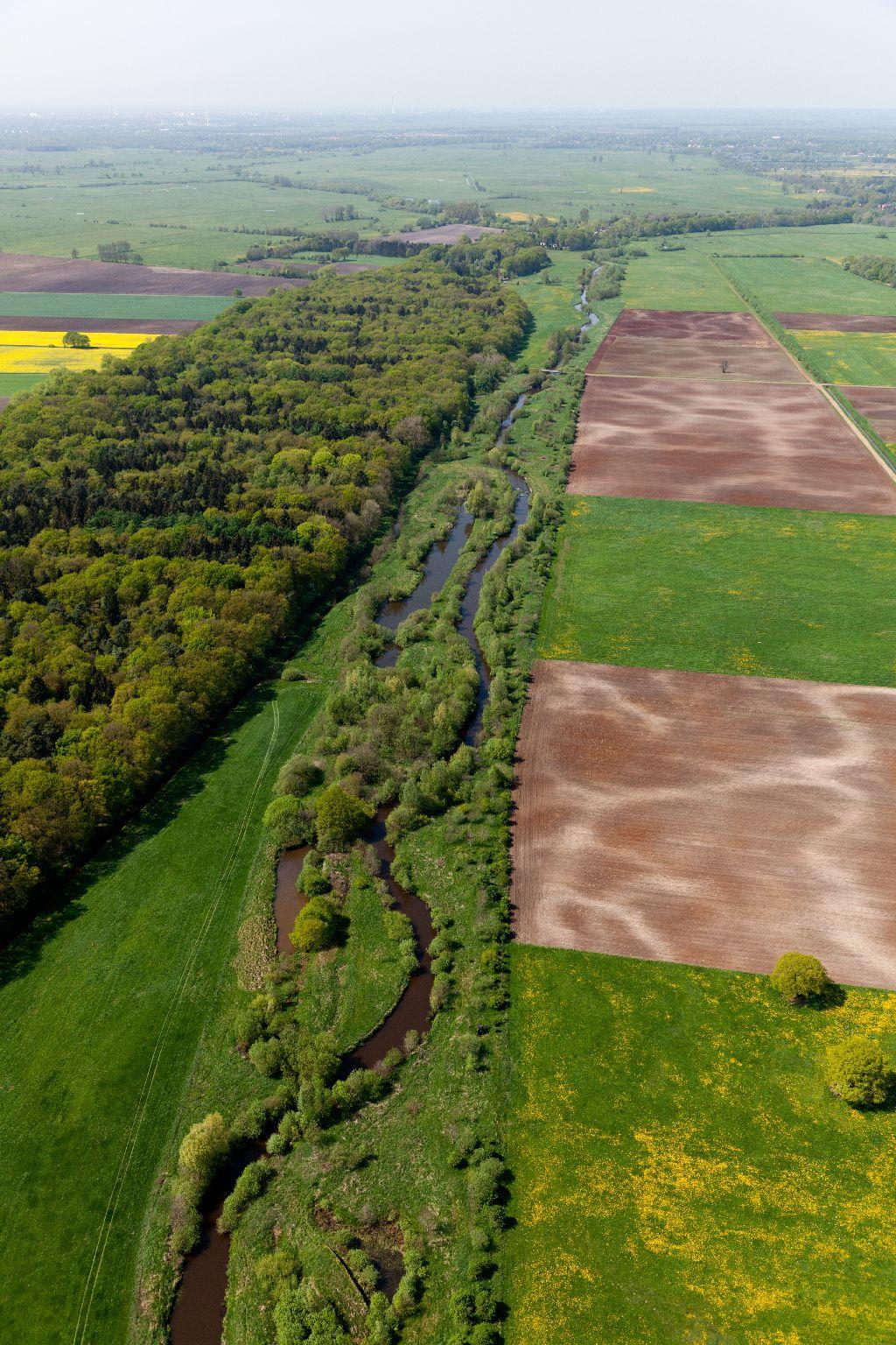 Luftbild eines renaturierten Abschnitts der Wümme. Mehrere Nebengerinne liegen entlang des geschwungenen Verlaufs des Hauptgewässers. Auf der einen Seite des Gewässers trennt ein Saum aus Gehölzen das Gewässer von den angrenzenden landwirtschaftlichen Flächen ab. Auf der anderen Seite finden sich Gras- und Waldflächen.