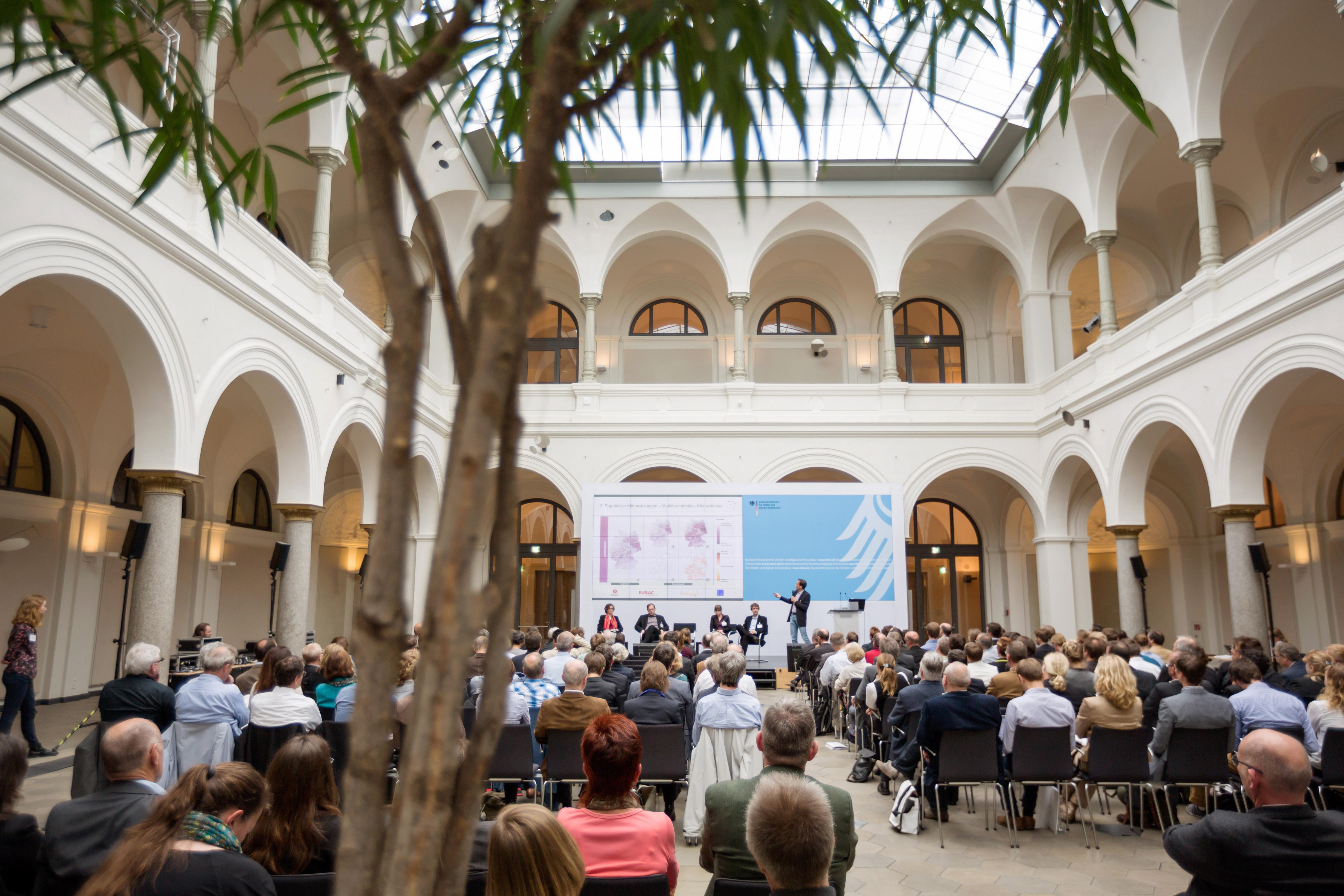 Das Publikum sieht einer Präsentation zur regionalen Auswirkung der Folgen des Klimawandels in Deutschland zu