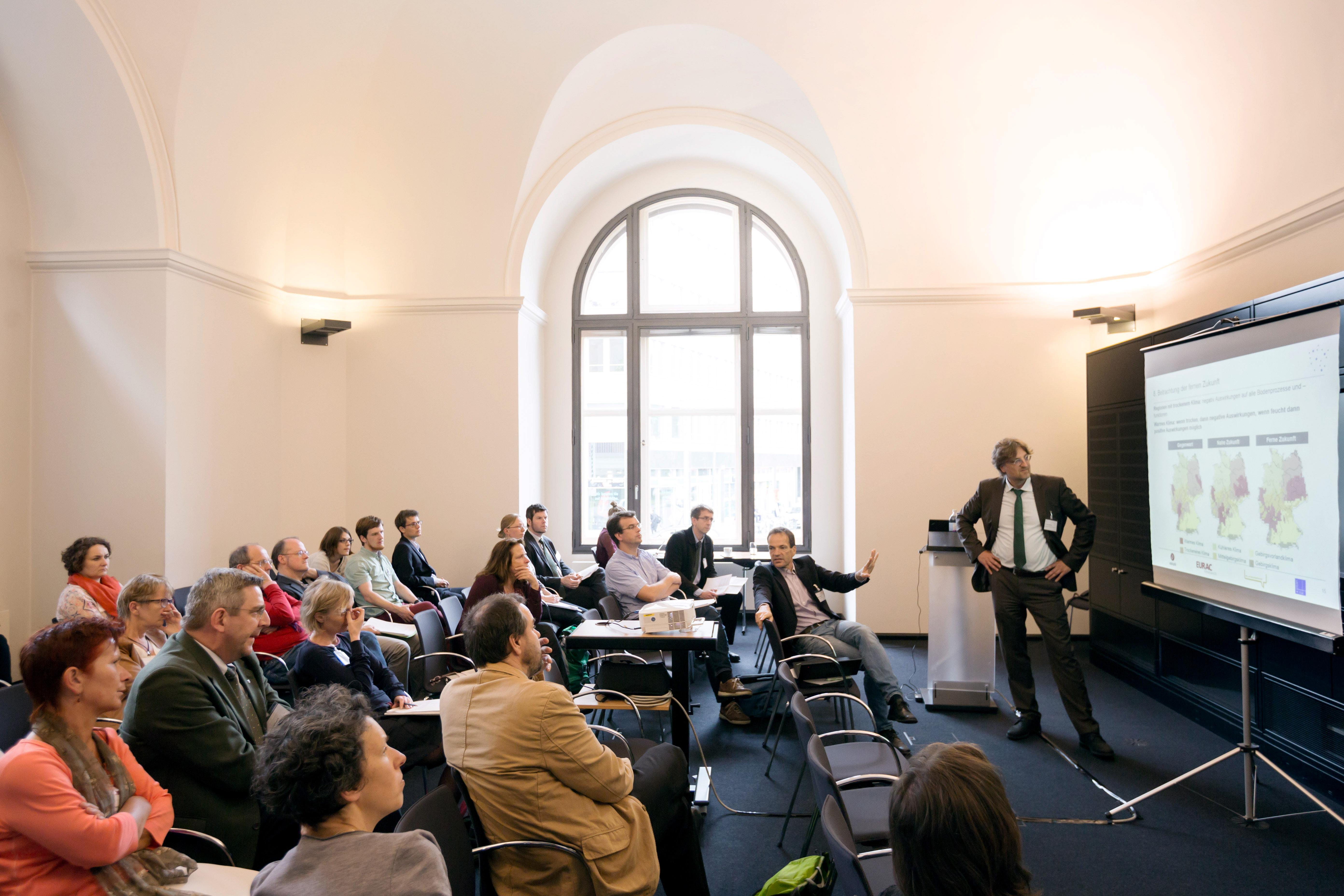 Ein Mann präsentiert seine Ergebnisse einem Publikum