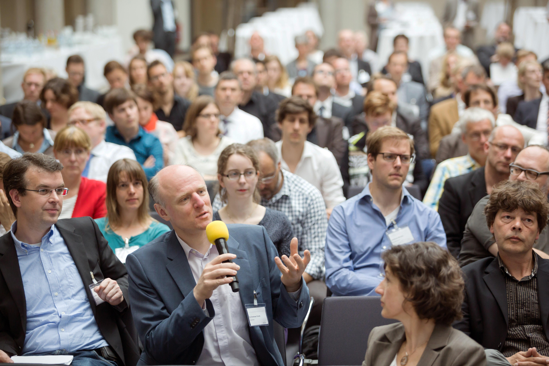 Ein Mann aus dem Publikum hält ein Mikrofon und spricht