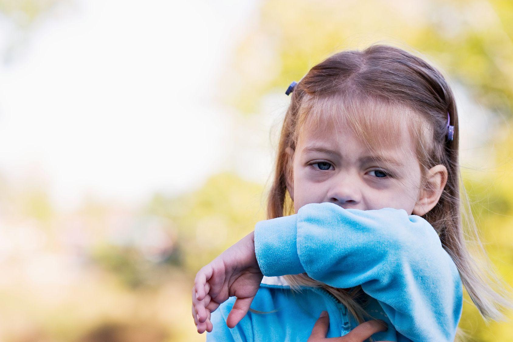 Ein Kind hustet in seinen Ärmel