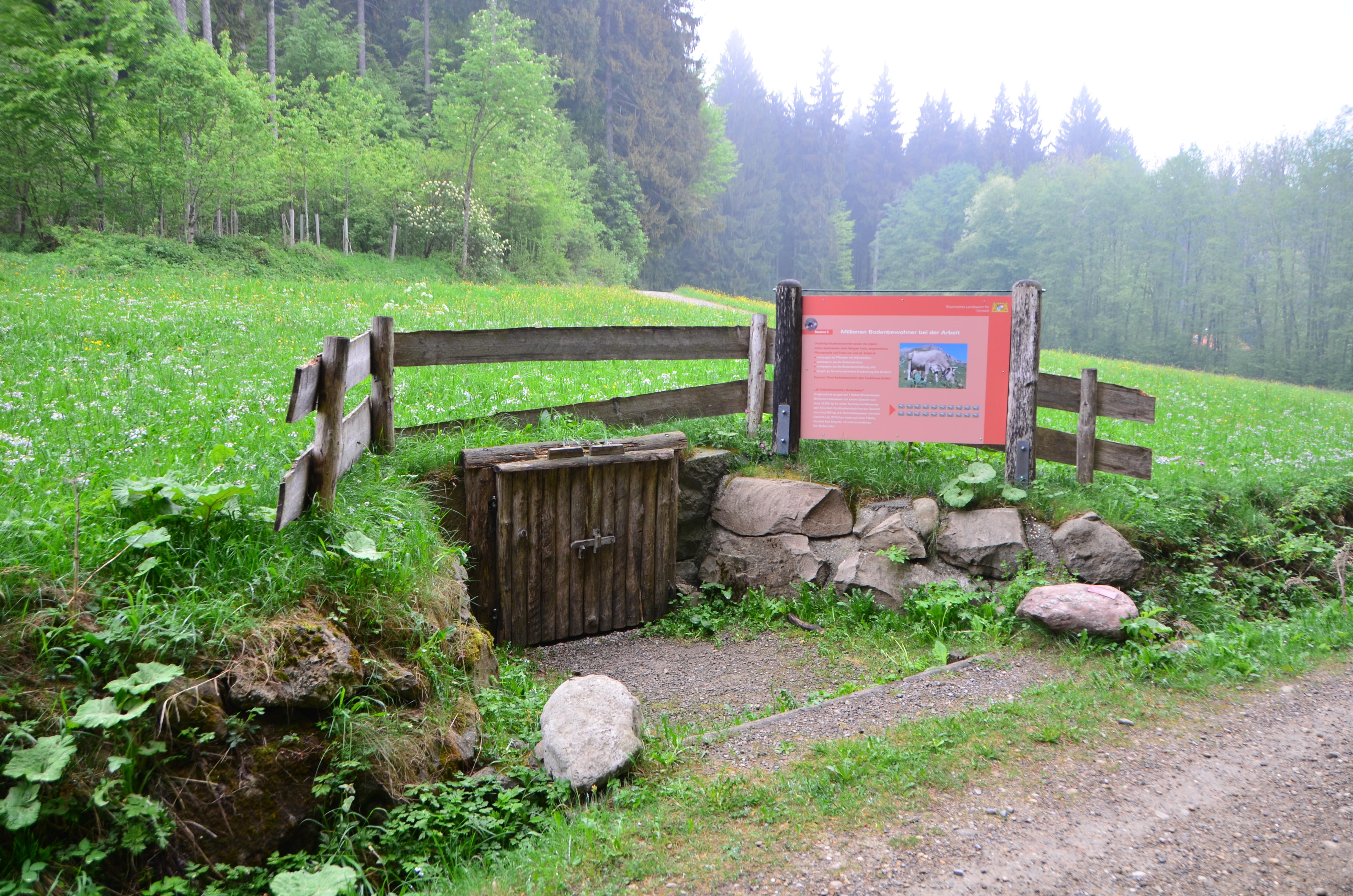 Ein Bodenprofil hinter einem Holztor und eine Tafel daneben
