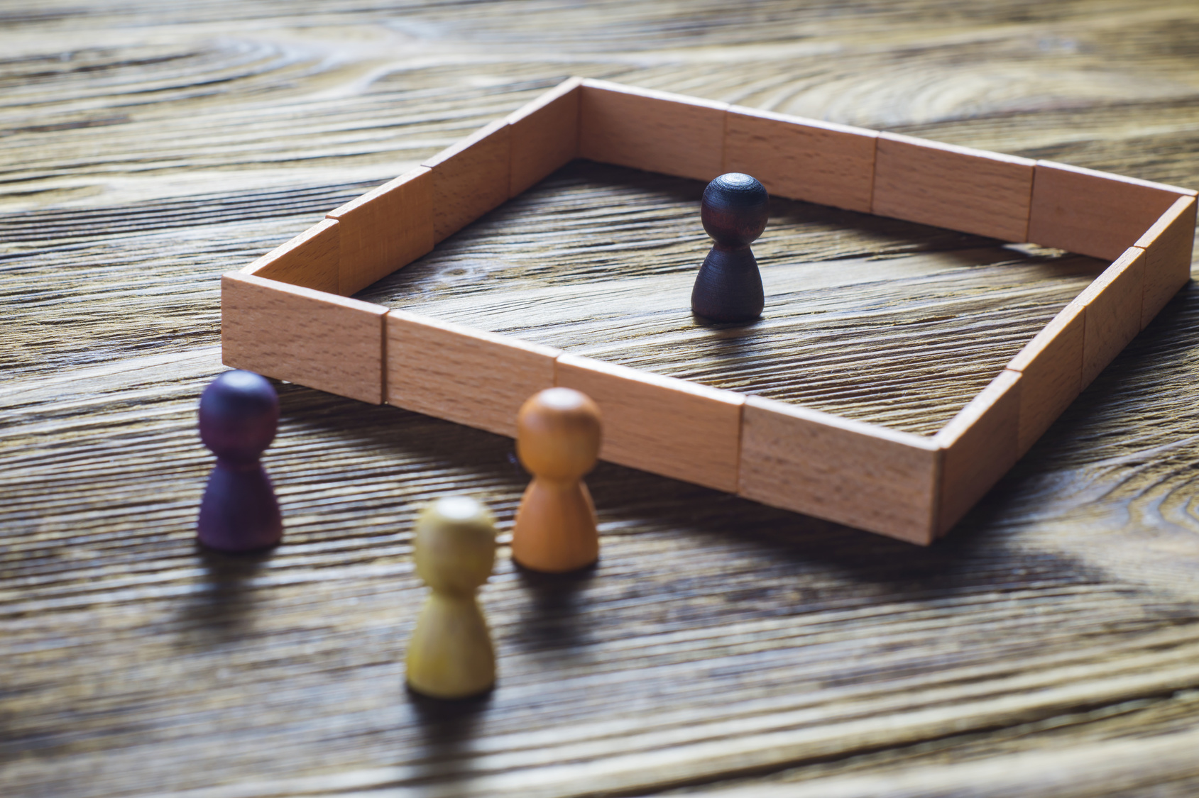 A token stands in the middle of a wooden square, three others stand outside.