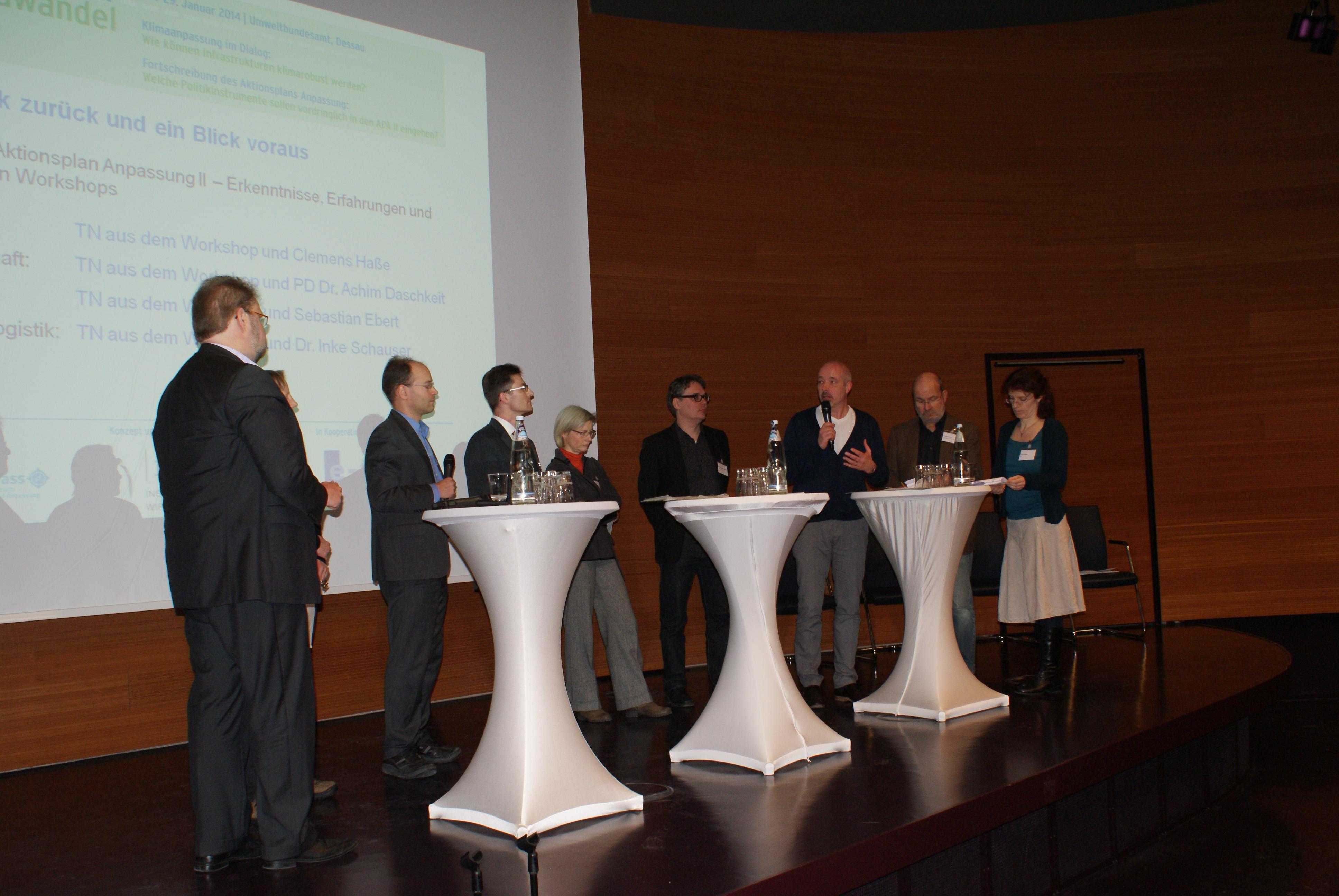 Teilnehmer der abschließenden Podiumsdiskussion stehen auf der Bühne um Stehtische herum Rede und Antwort