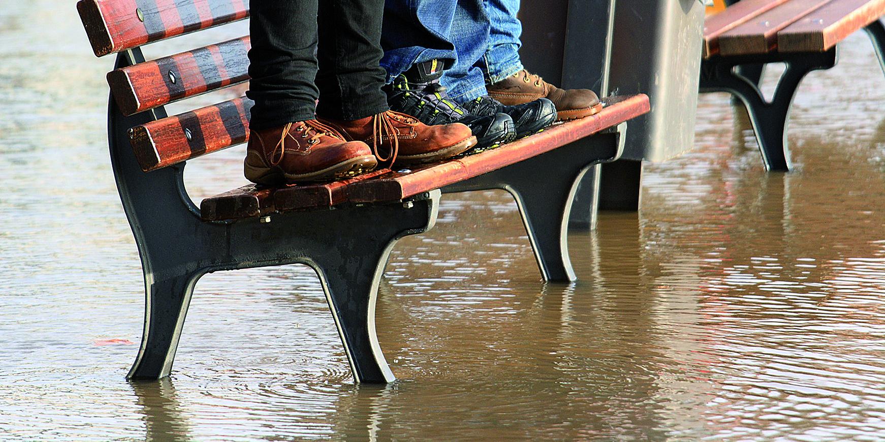 Menschen stehen auf einer Sitzbank die von Wasser umspült ist.