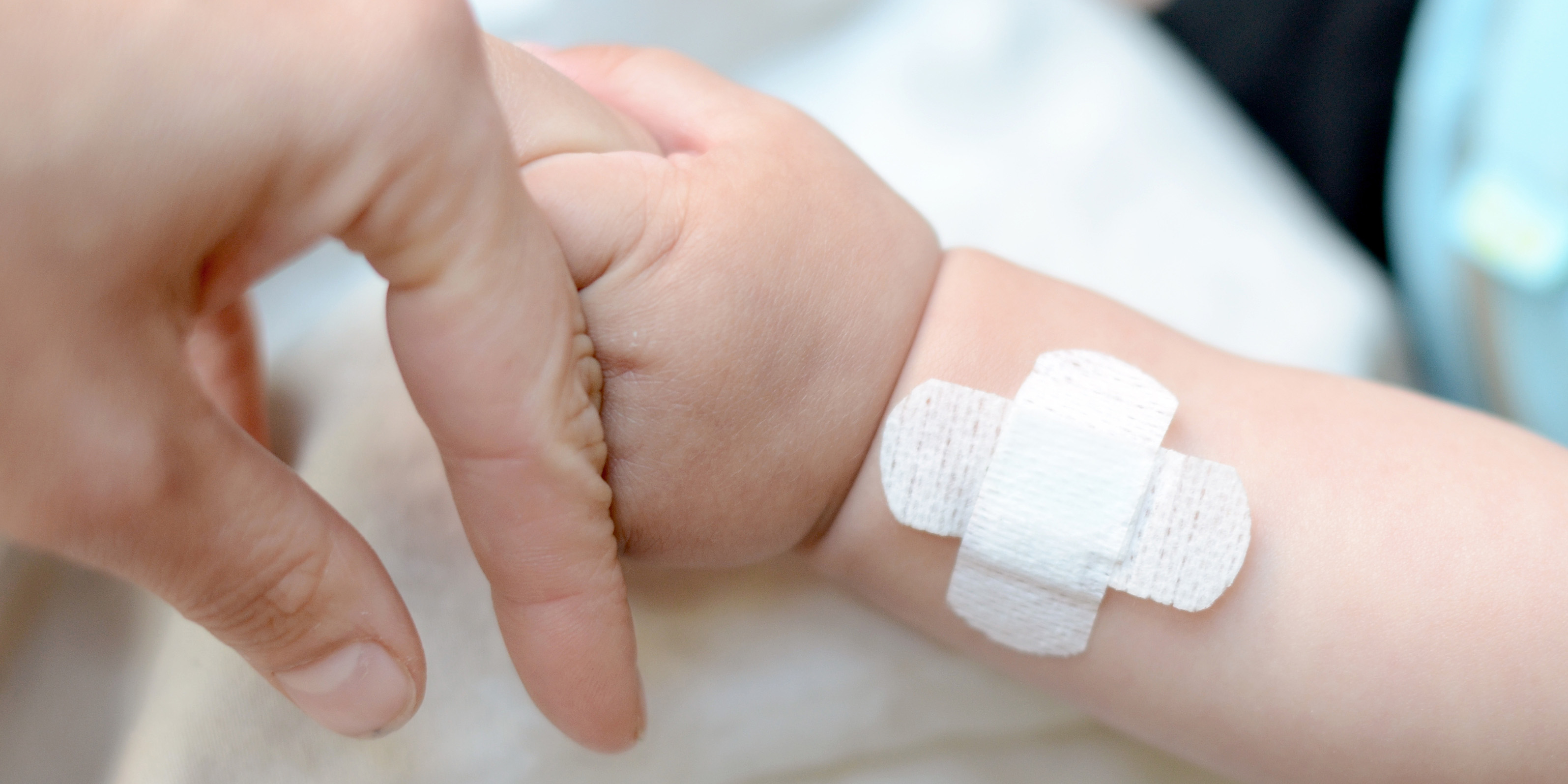 A baby hand holding the finger of an adult