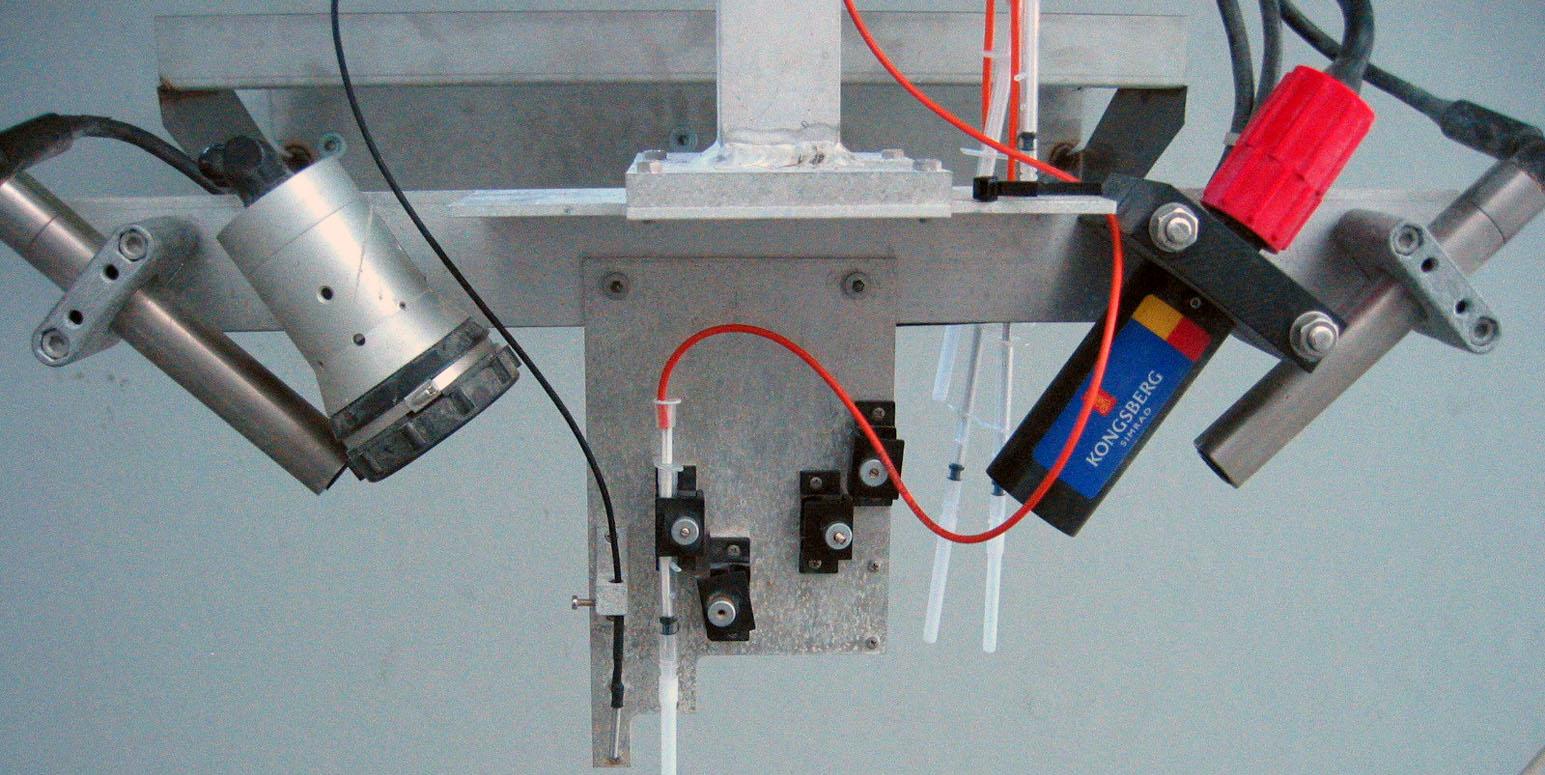 an einer kleinen Metallplatte an einem Metallarm sind nach unten zeigend Geräte befestigt, die an Taschenlampen oder Mikrofone erinnern