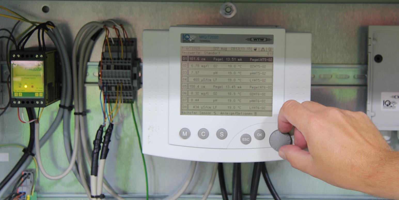 an einer Metallschine an einer Wand sind elektrische Messgeräte angebracht mit digitalen Anzeigen und Tasten, eine Hand dreht an einem Drehschalter