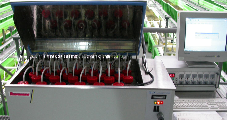 Messgerät in Form eines grauen Metallkastens, an dem oben der Deckel aufgeklappt ist, darin Gefäße mit roten Deckeln, aus denen Schläuche ragen