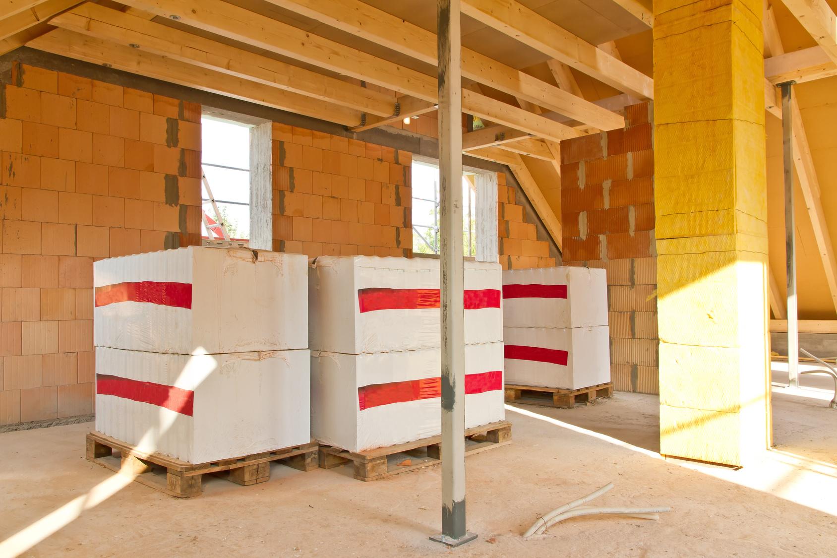 Haus im Rohbau von innen, Paletten mit neuem Baumaterialien