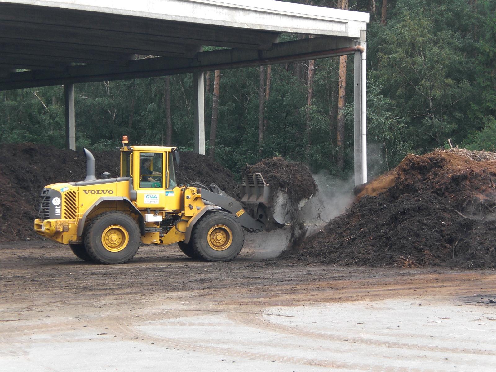 ein Radlader setzt einen großen Haufen Kompost um