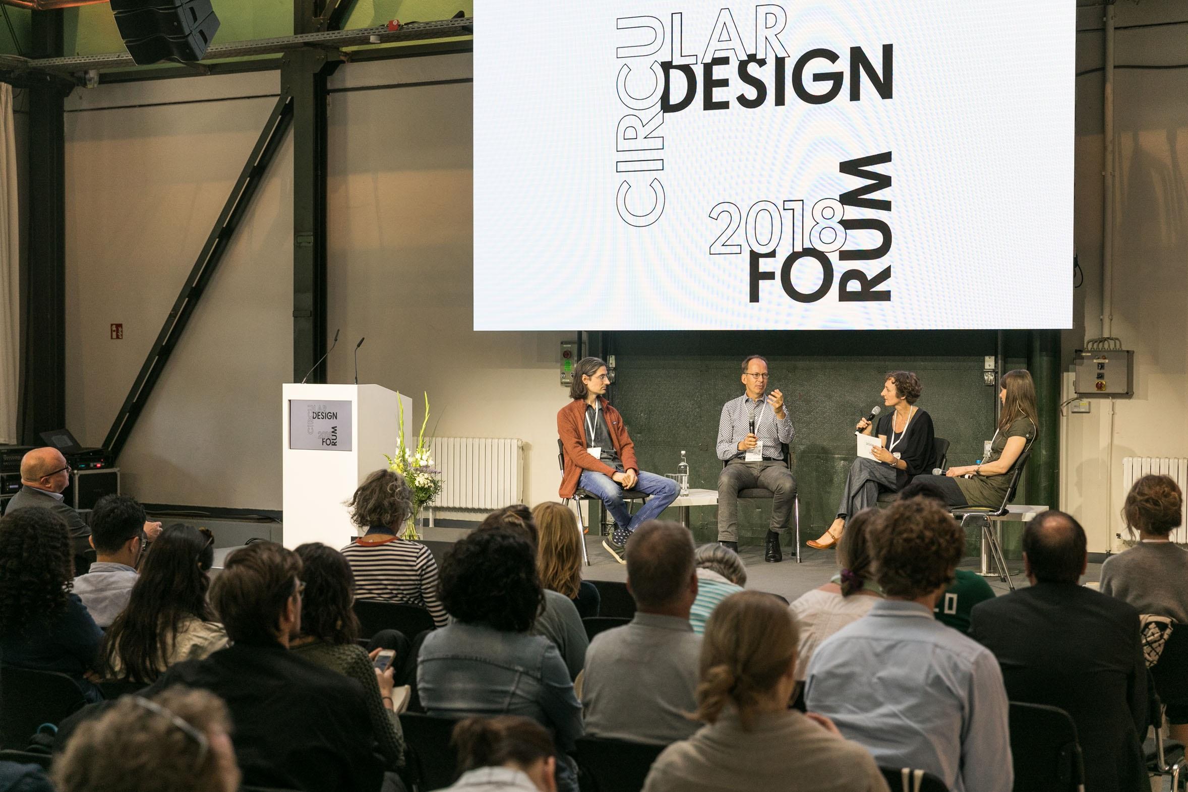 """zwei Männer und zwei Frauen diskutieren mit Mikrofonen in einem Halbkreis sitzend auf einer Bühne vor Publikum, darüber ein Banner mit der Aufschrift """"Circular Design Forum 2018"""""""