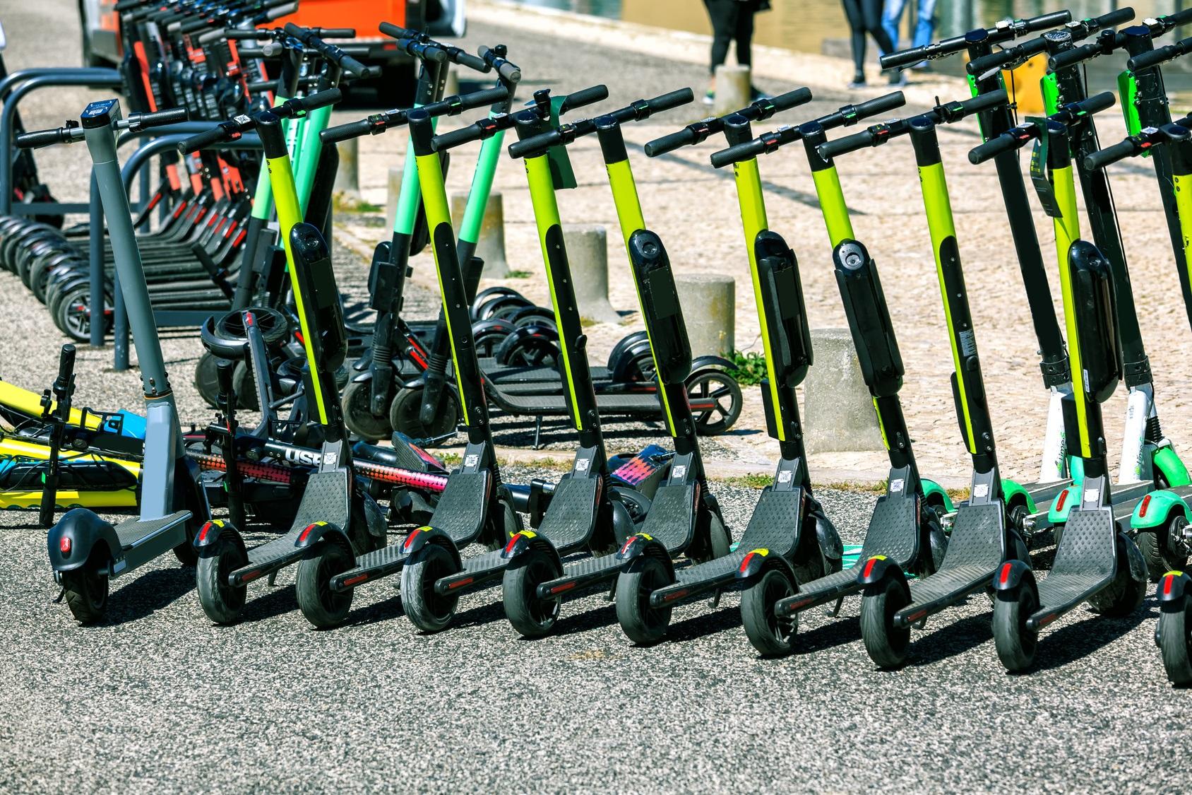 viele Leih-E-Tretroller in einer Reihe abgestellt in der Stadt
