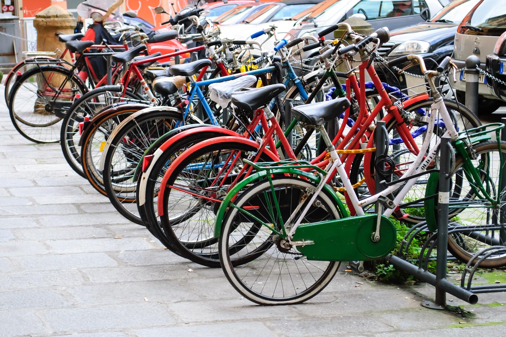viele bunte Fahrräder in Fahrradständern abgestellt