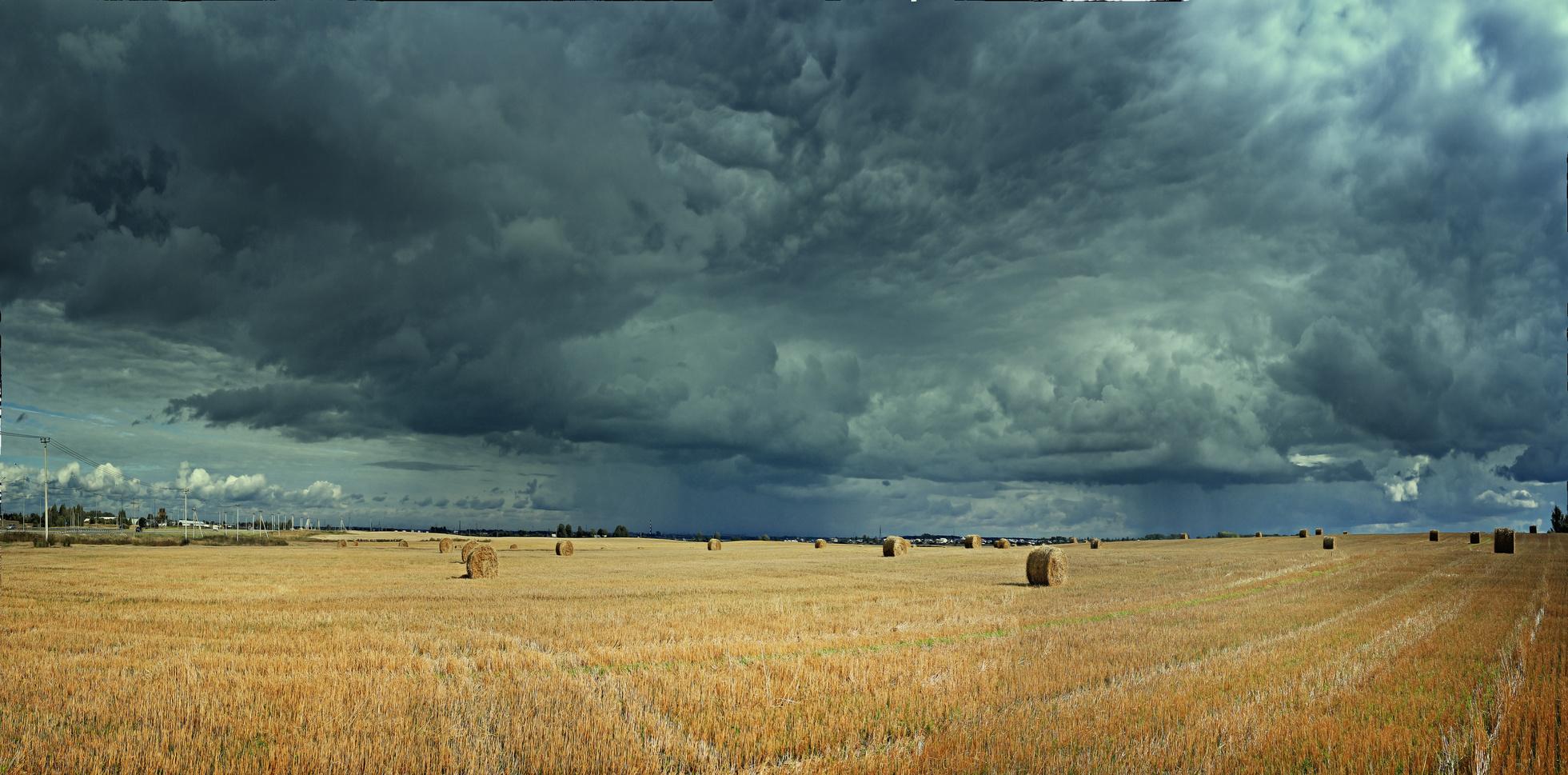 abgeerntetes Getreidefeld mit gelben Stoppeln und Strohballen. Am Himmel türmen sich bedrohlich dunkle und niedrig hängende Wolken.
