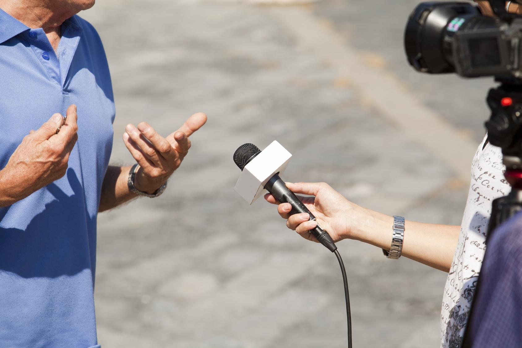 Mann wird interviewt und gefilmt