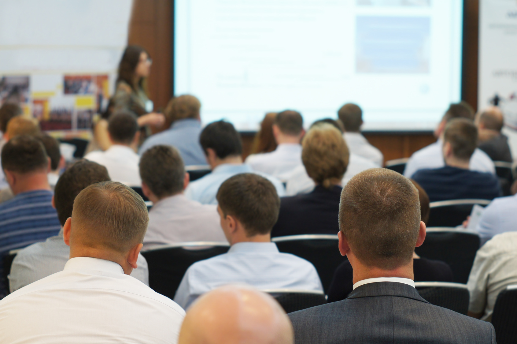 Besucher eines Vortrags mit Präsentation sitzen in Reihen