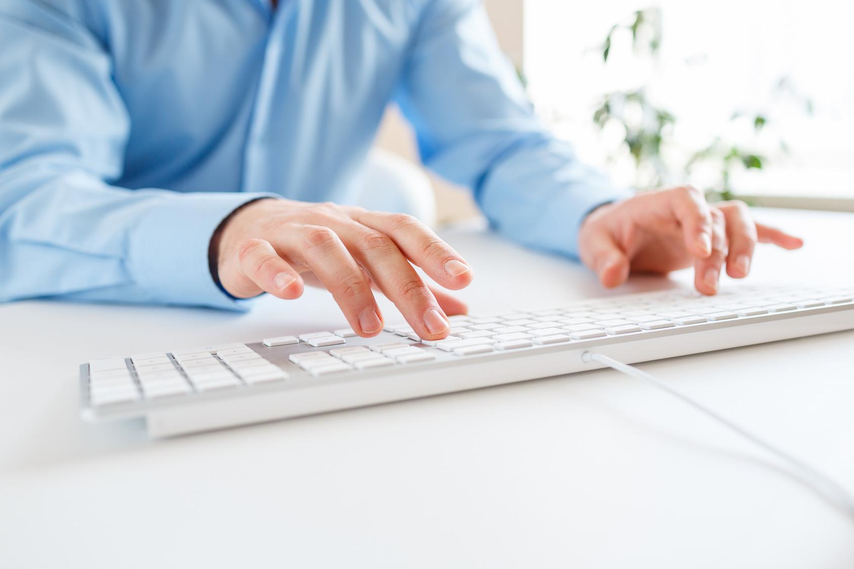Mann tippt auf einer Computertatstatur