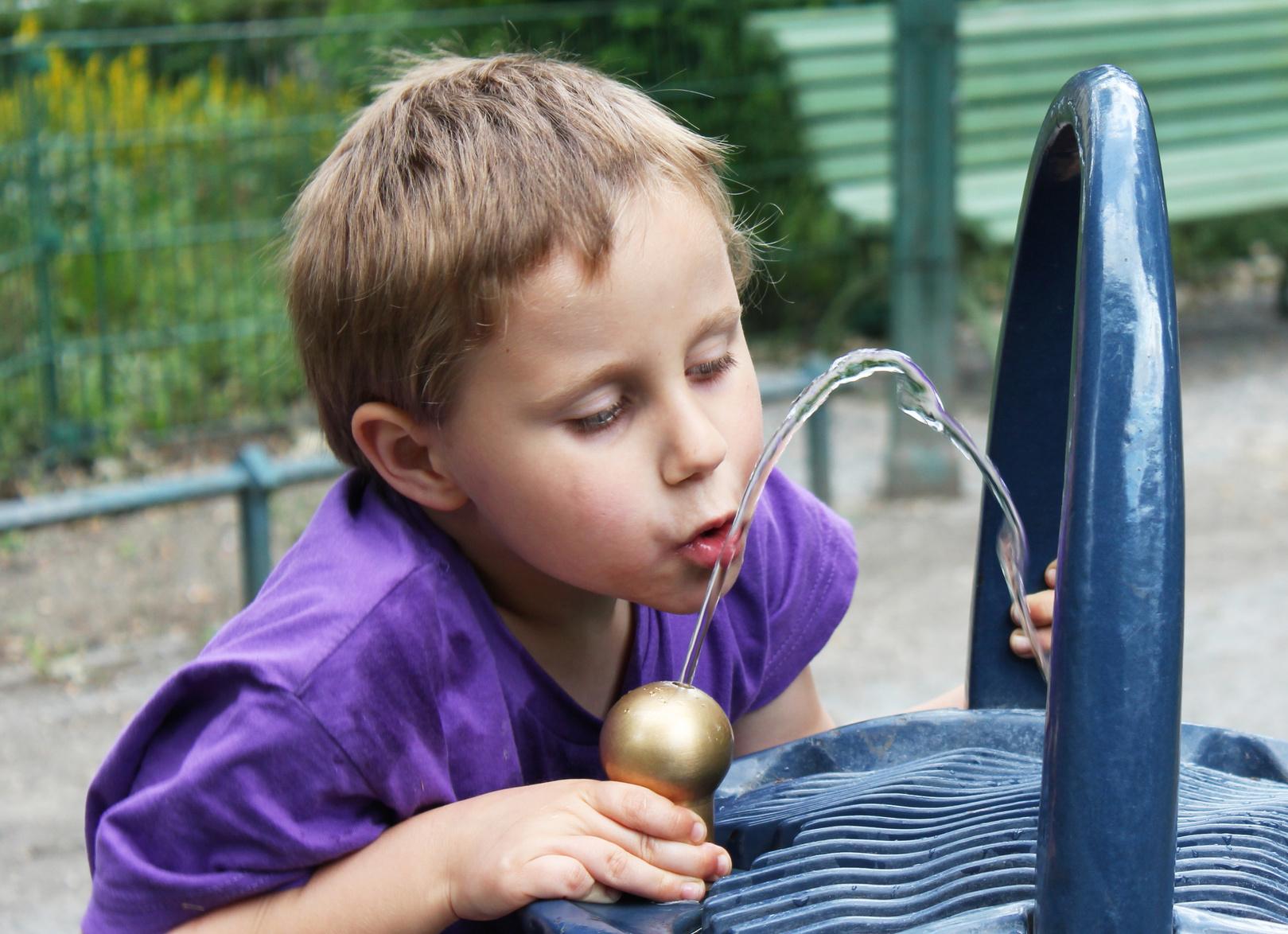 Junge trinkt an einem Trinkbrunnen im Park
