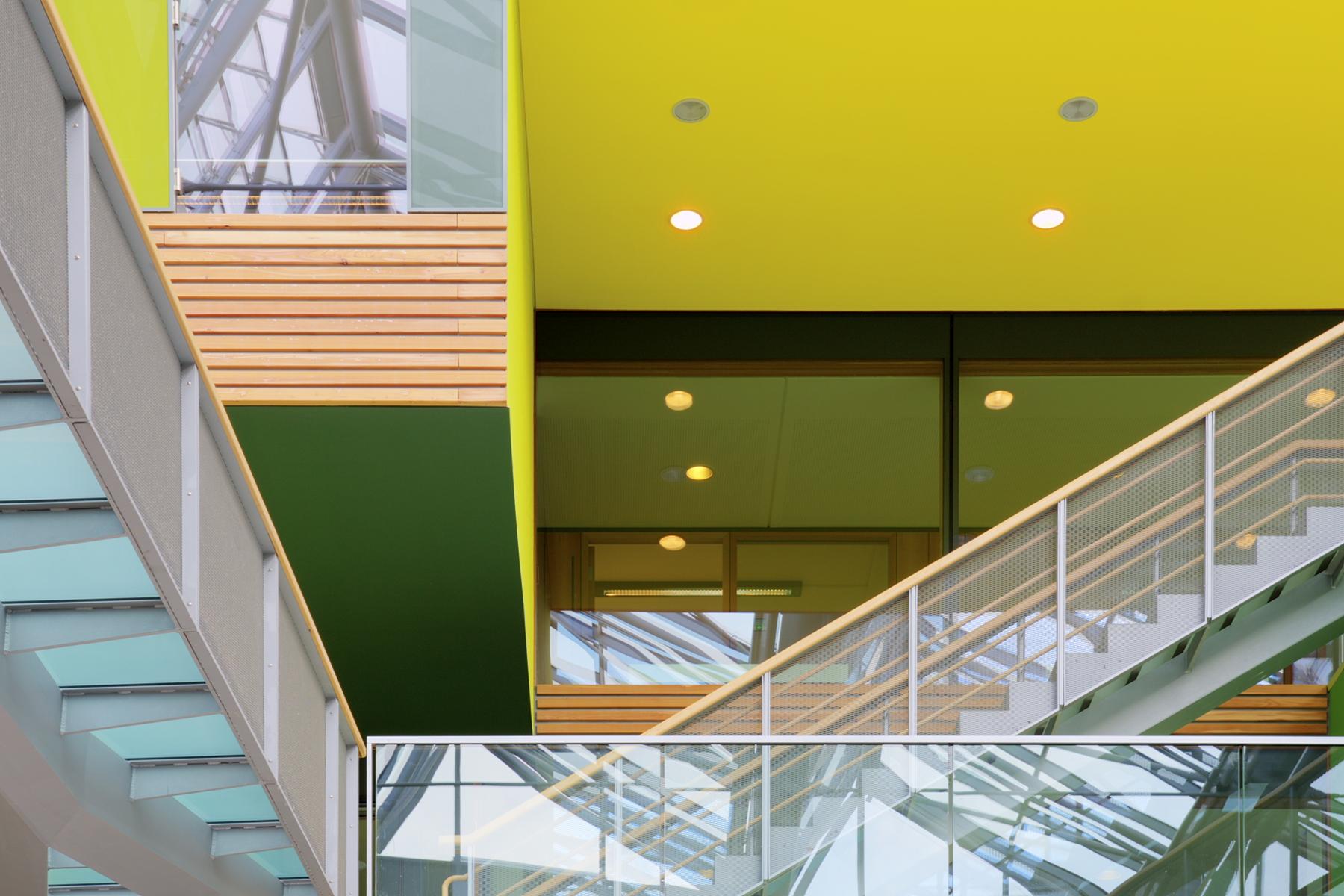 Brücken und Treppen mit gläsernen Geländern im Innenhof, Innefassade aus Holz, gelben und grünen Flächen