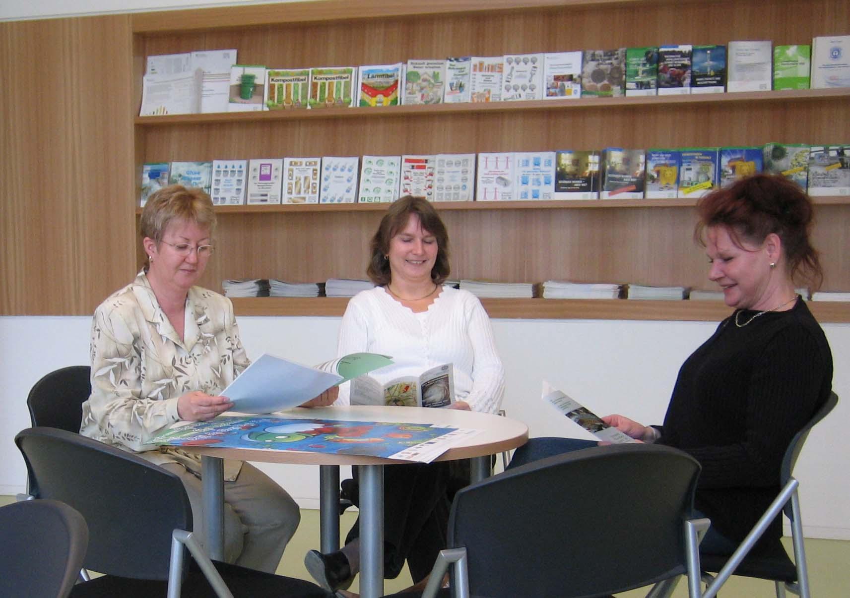 drei Frauen sitzen an einem runden Tisch und schauen Faltblätter und Broschüren an, im Hintergrund ein Regal mit weiteren Faltblättern und Broschüren