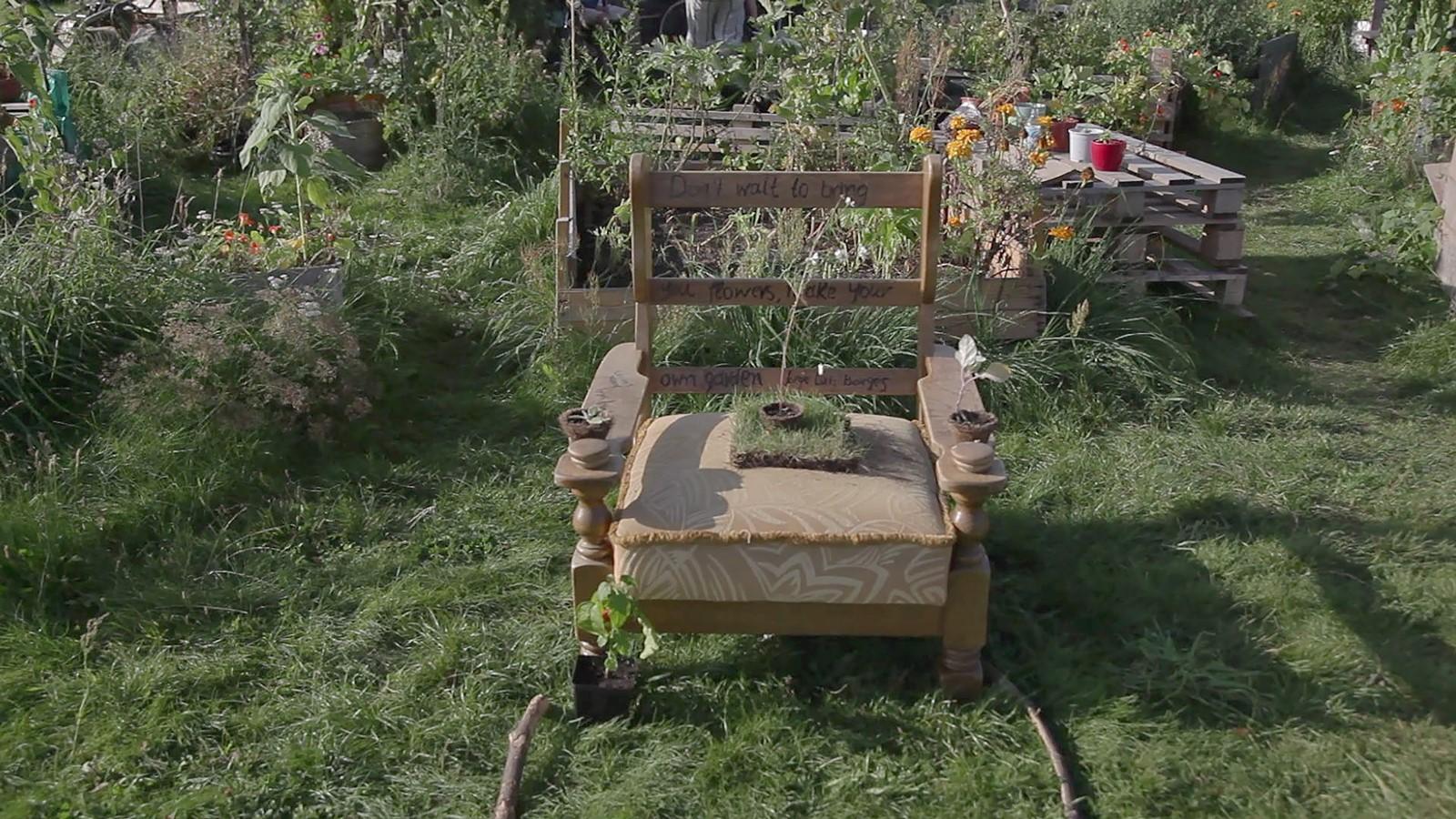 Ein Garten mit mehreren Beeten, in der Mitte steht ein alter Sessel, aus dem eine Pflanze wächst.