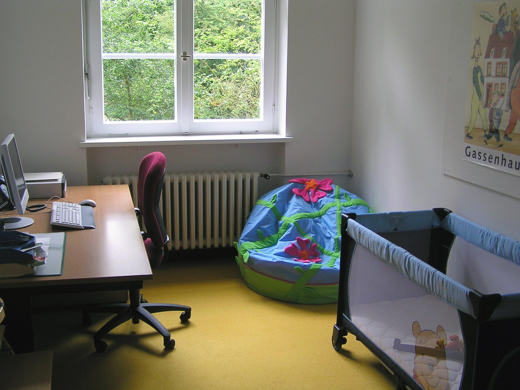 Eltern-Kind-Zimmer: gegenüber vom Schreibtisch steht ein Bett für Kleinkinder, in der Ecke liegt ein bunter Sitzsack
