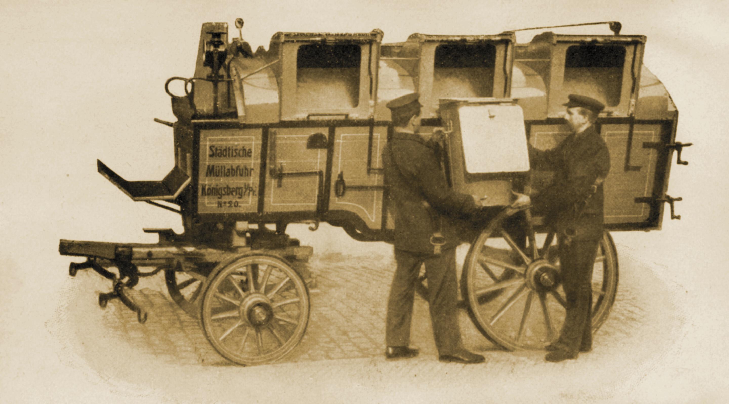 Zwei Arbeiter laden eine Tonne auf einen Wagen