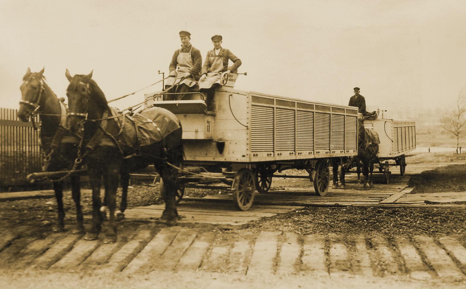 Pfedewagen mit zwei Arbeitern auf dem Kutschbock, die Ladefläche ist mit Metall-Rolläden abgedeckt.