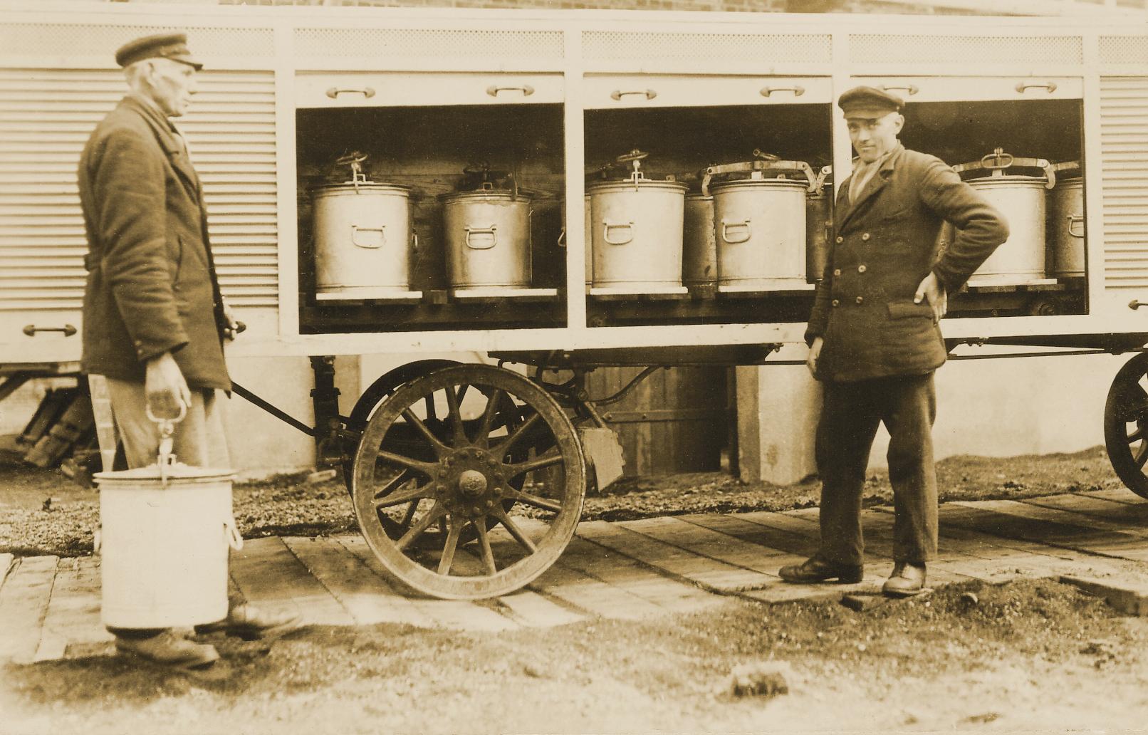 Zwei Arbeiter laden Eimer auf einen Wagen mit Rolläden