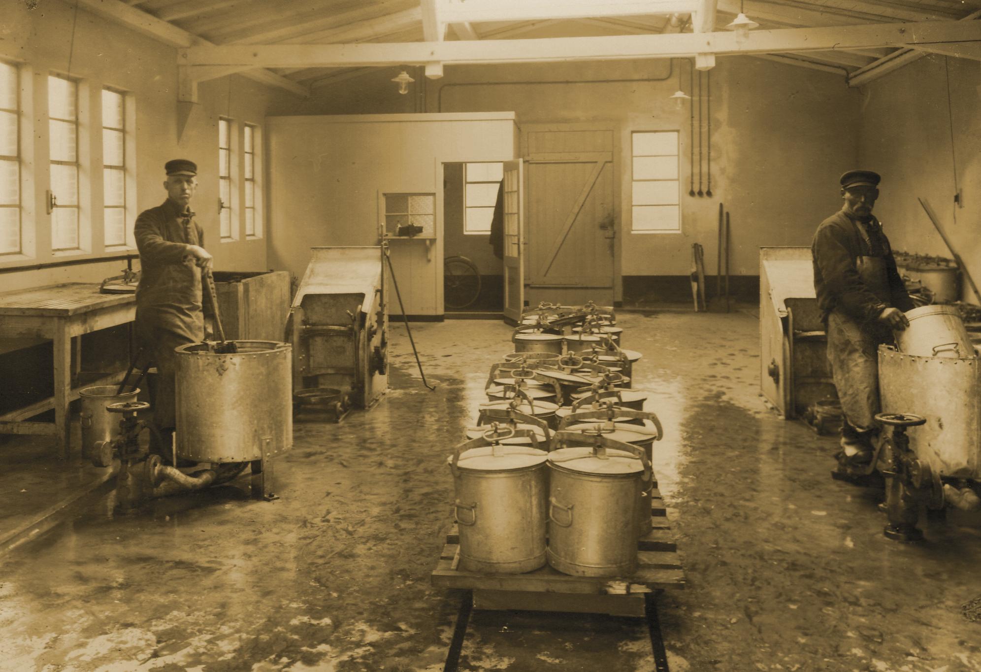 Entleerung und Wäsche der Wechselkübel durch zwei Arbeiter in einer Waschküche