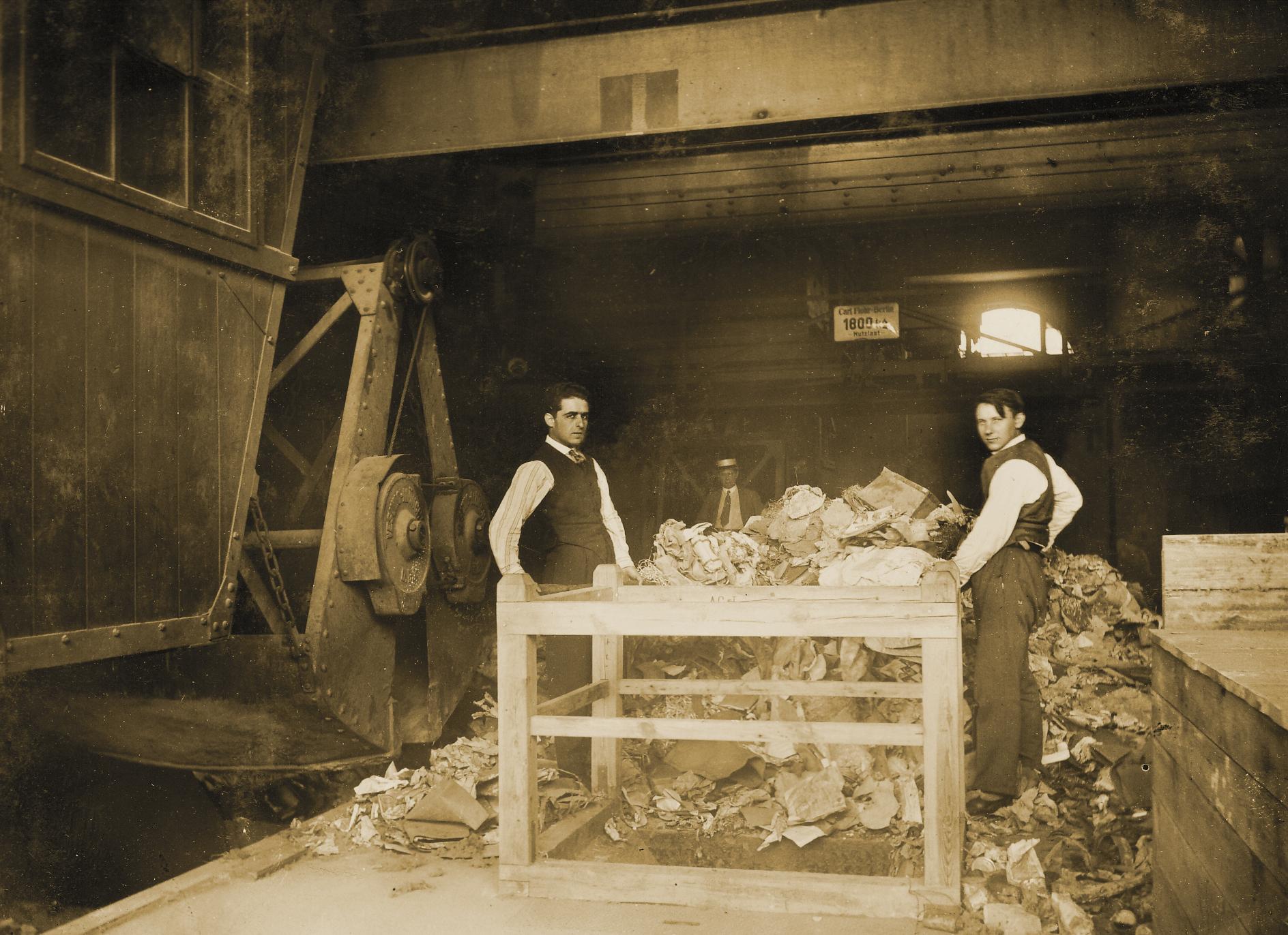 Zwei Arbeiter stehen zwischen einem Tisch, einem Berg Müll und einem Kran.