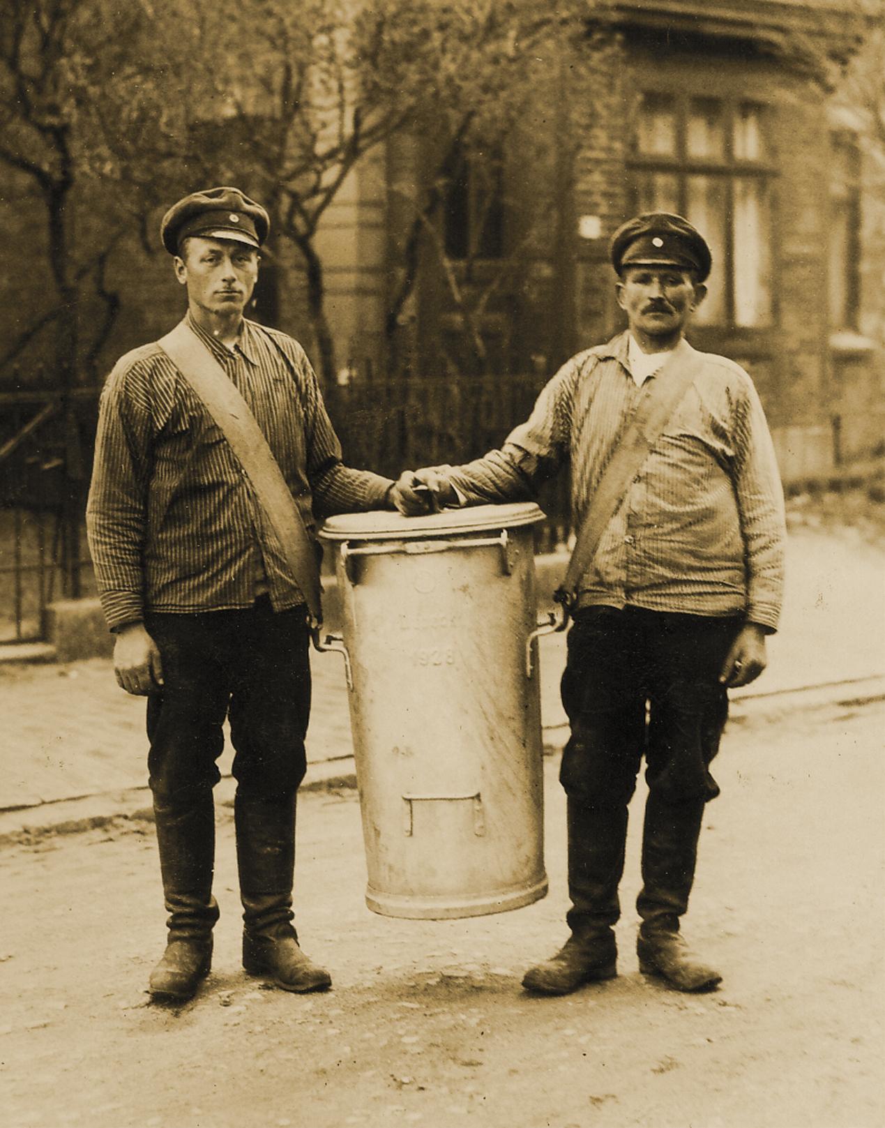 Zwei Männer tragen einen großen Standeimer