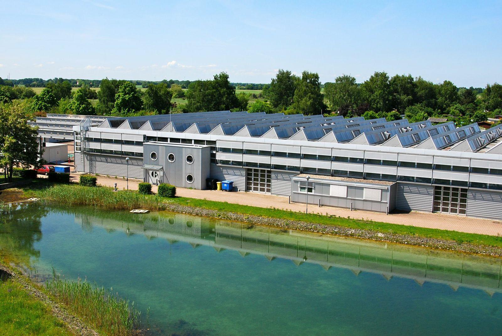 Moderne Halle mit Shed-Dach, davor ein großes rechteckiges Wasserbecken