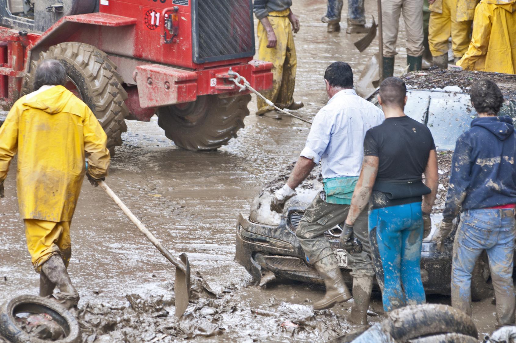 Männer räumen mit Schaufeln und Bagger den Schlamm nach dem Hochwasser weg