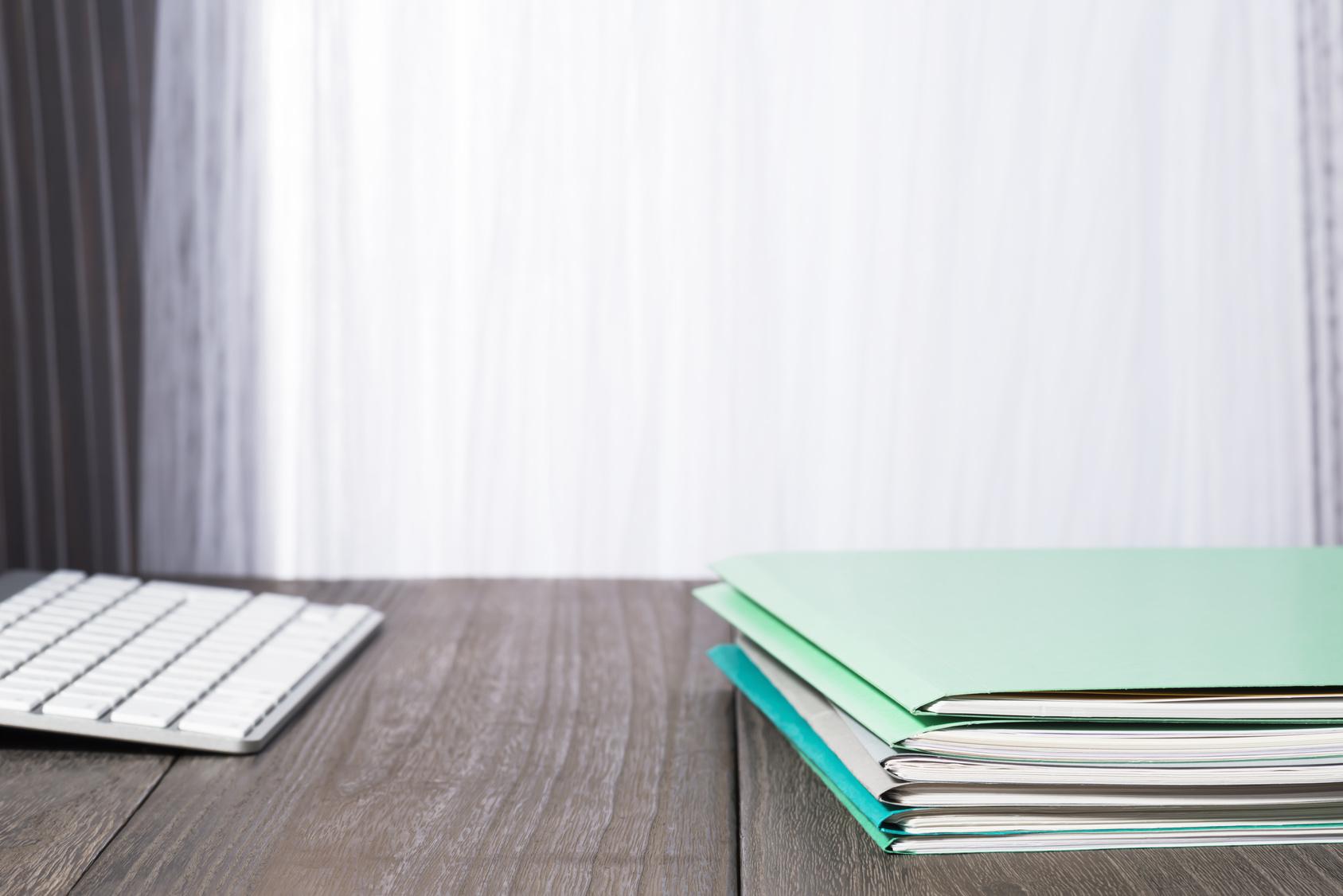 Tastatur und grüne Mappen auf einem Tisch
