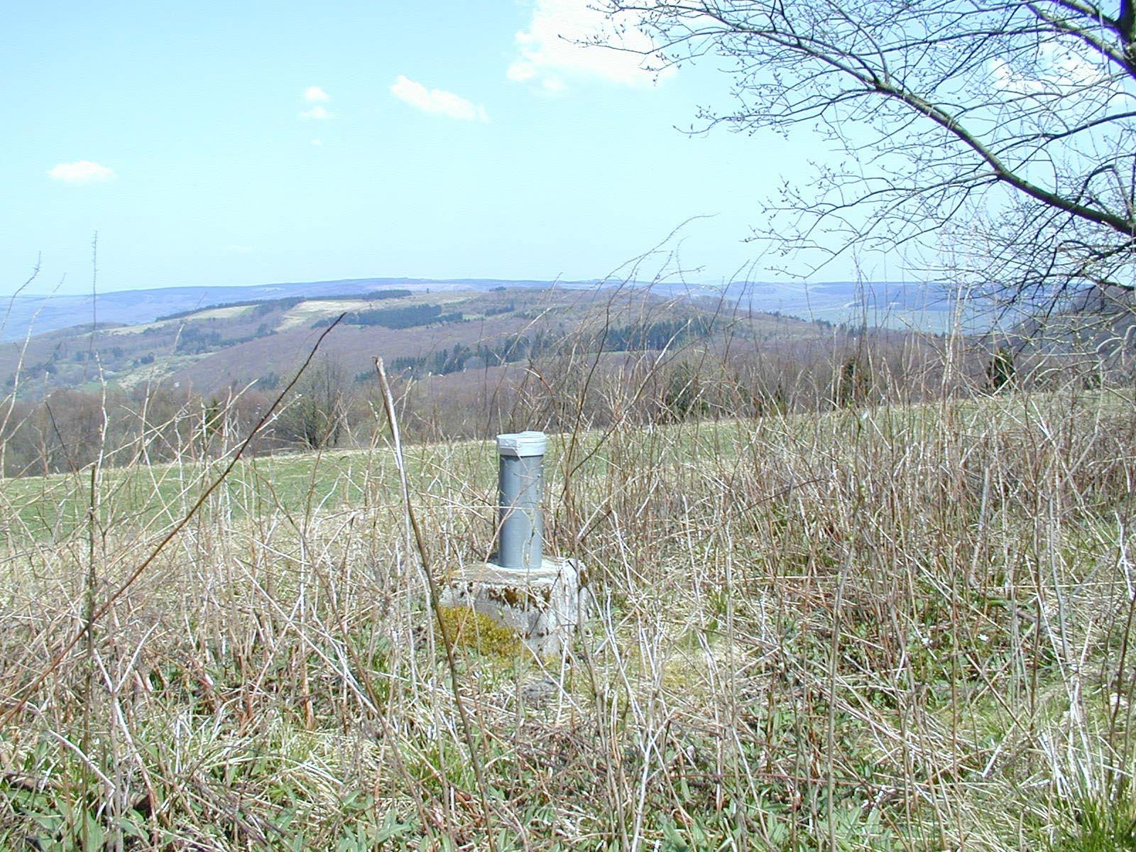 Grundwassermessstelle vor Landschaft.