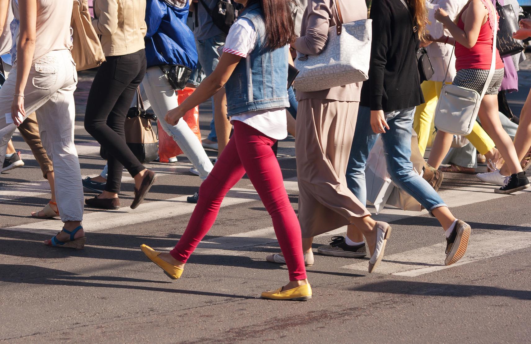 Detailfoto Fußgänger überqueren eine Straße mit Zebrastreifen.