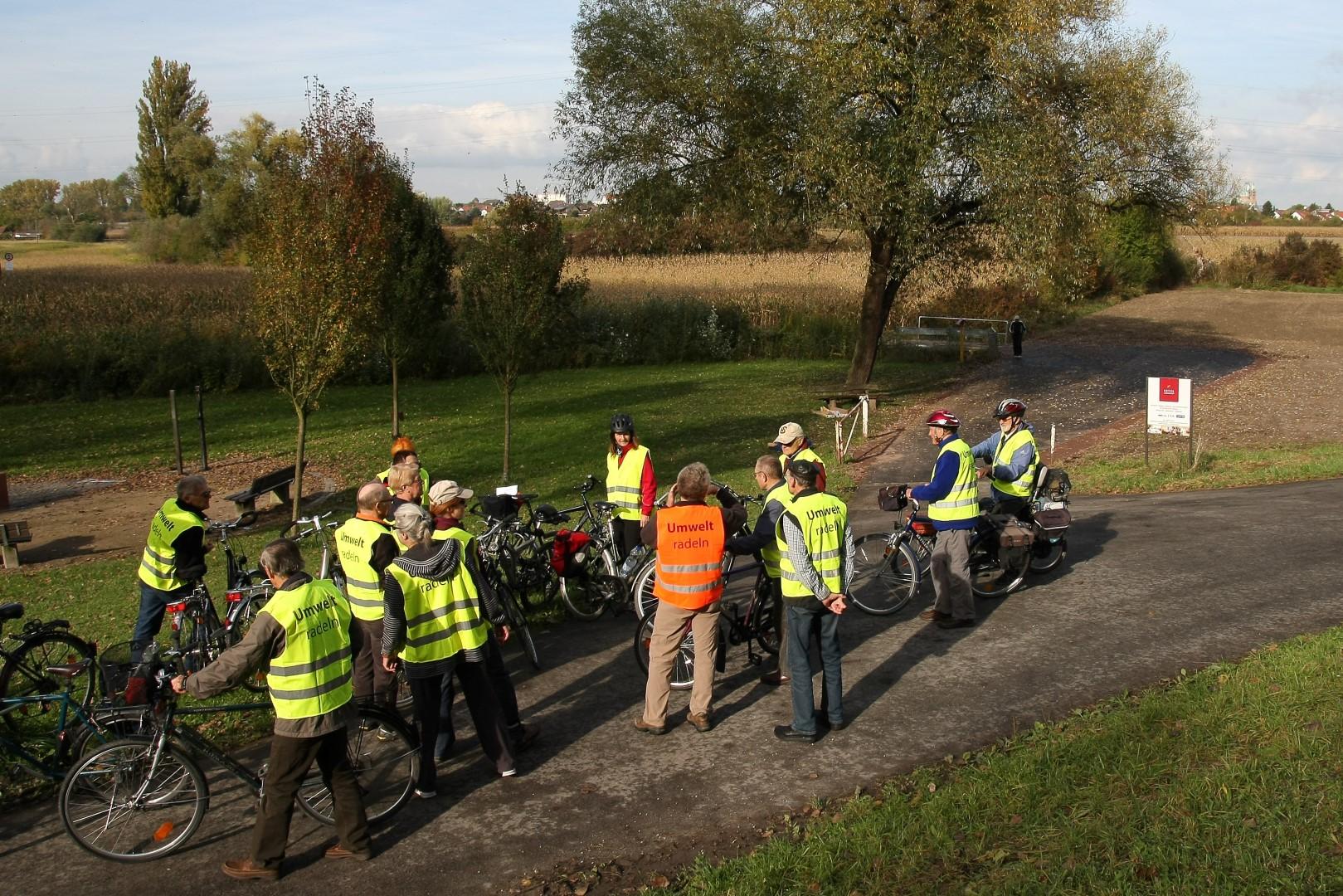 """Ein Gruppe von Fahrradfahrerinnen und -fahrern, die alle Westen mit der Aufschrift """"Umweltradeln"""" tragen,  im Feld"""