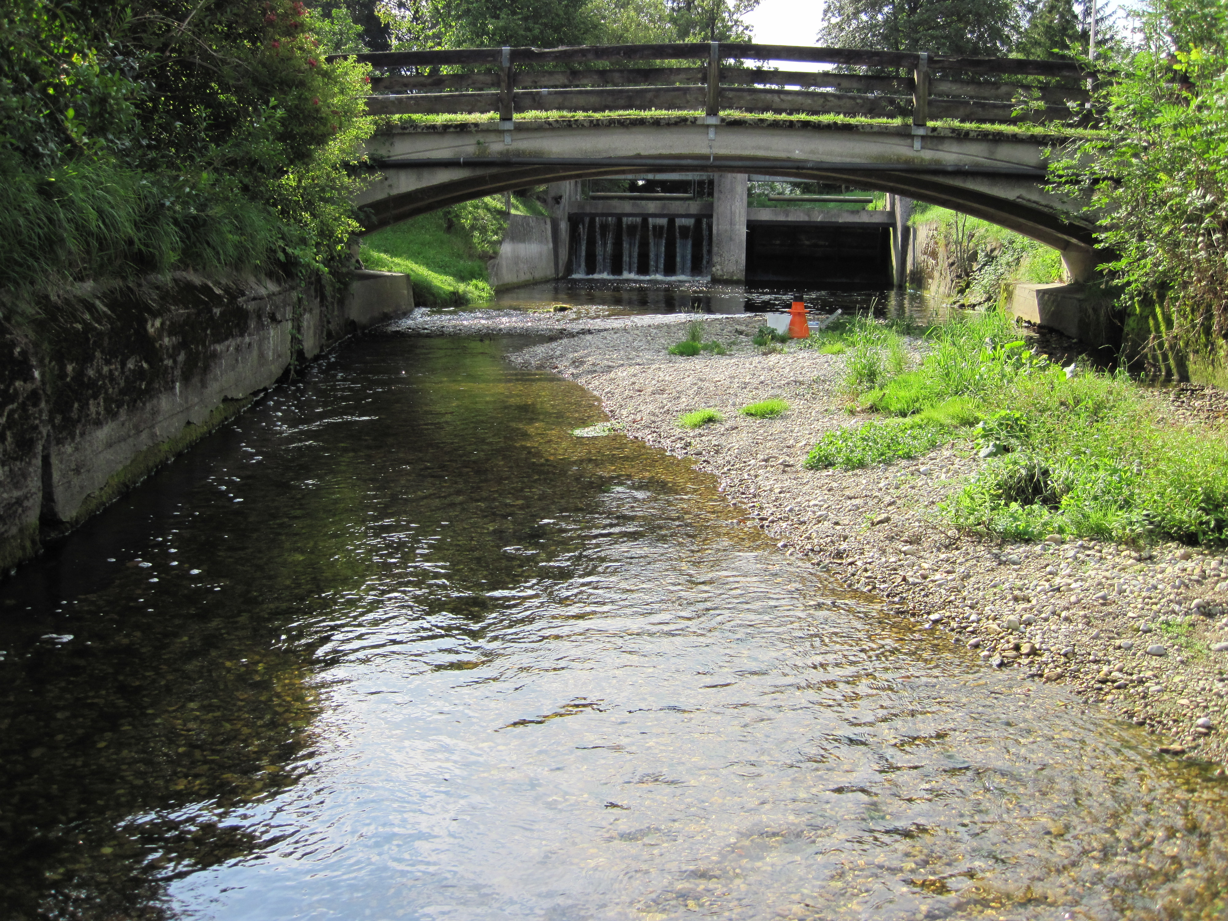 Flussansicht mit Brücke und im Hintergrund ist eine kleinere Stauanlage zu sehen