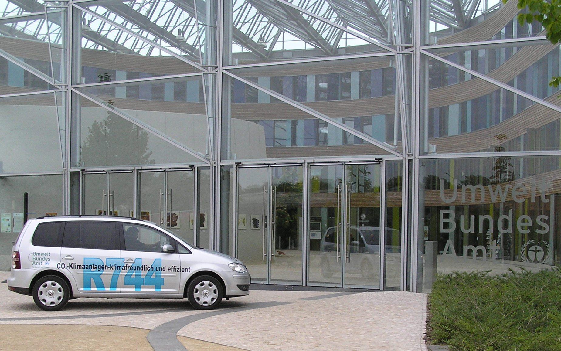 Ein silberner VW Touran steht vor Glastüren. Auf dem Auto steht in scharzer Schrift: CO2-Klimaanlagen - klimafreundlich und effizient
