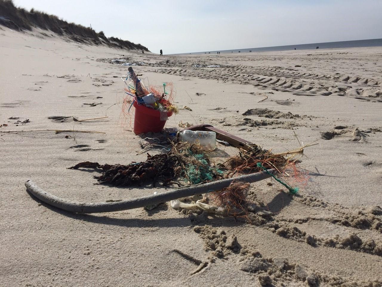 Müll liegt am Sandstrand, vor allem Plastik- und Fischereimüll.