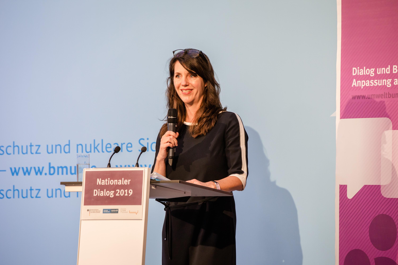 Dies ist ein Bild von dem Nationaler Dialog 2019: Klimawandelfolgen in Deutschland – Bereit zu handeln für bessere Vorsorge. Man siehr eine weibliche Perosn mit langen schwarzen Haaren eine Rede halten. Sie steht auf einer Bühne, an einem Pult und strahlt in die Kamera.