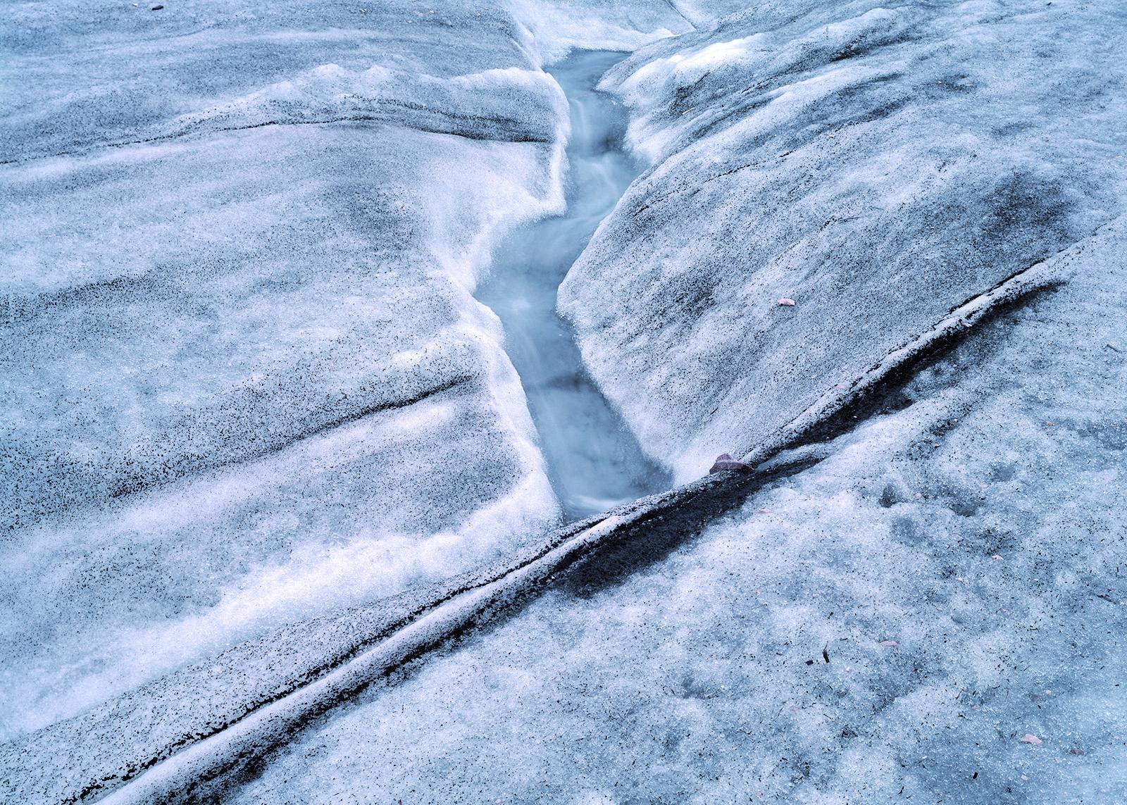 Schmelzwasser läuft eine kleine Rinne entlang.