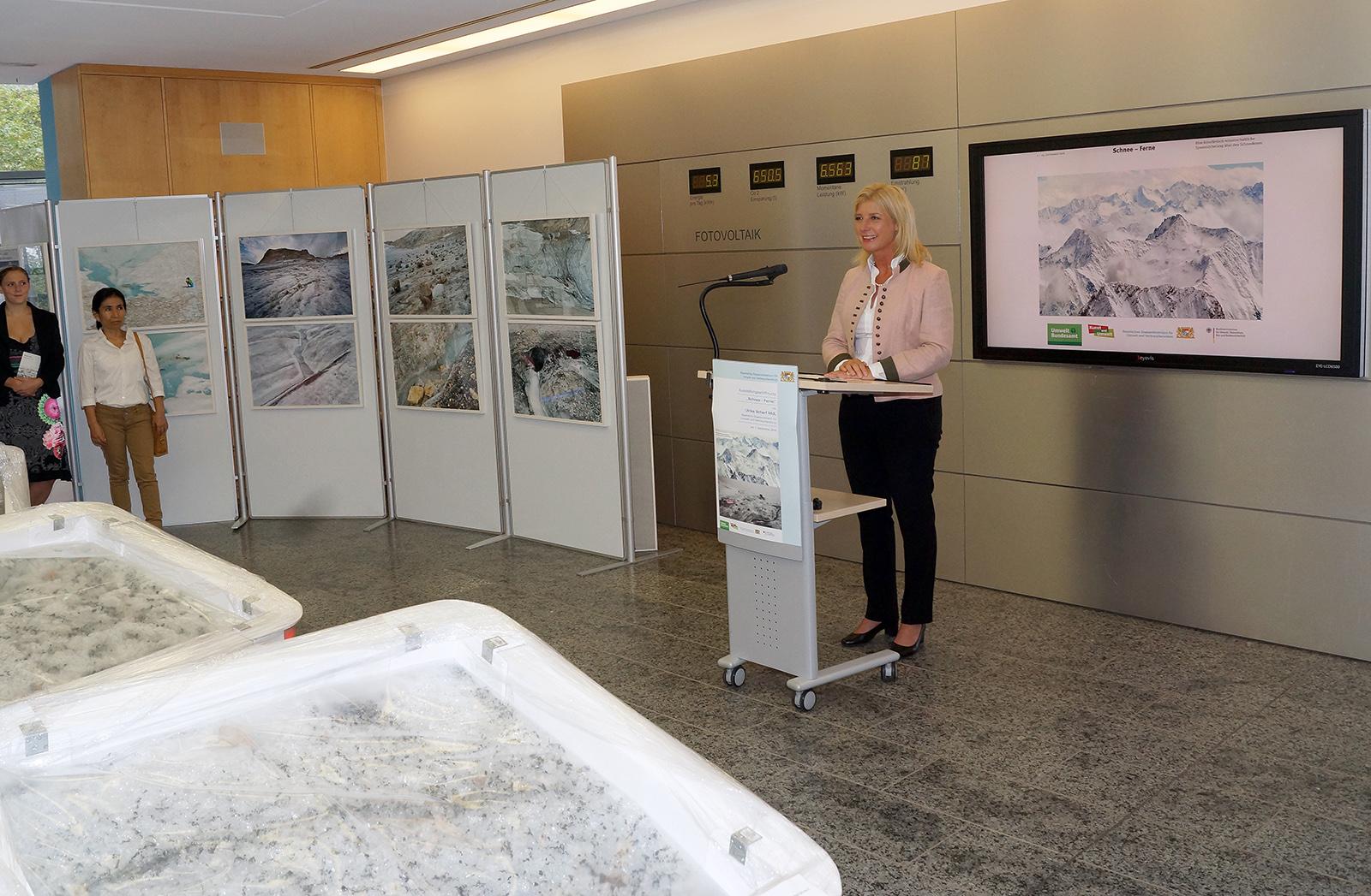 Staatsministerin Ulrike Scharf an einem Rednerpult. Um sie herum die ausgestellten Fotografien.